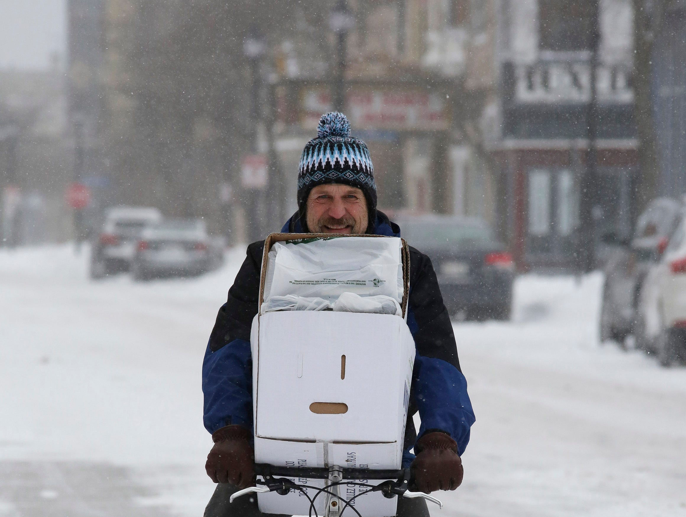 A bicyclist pedals down North 8th Street with a load on his handlebars, Saturday, January 19, 2019, in Sheboygan, Wis.