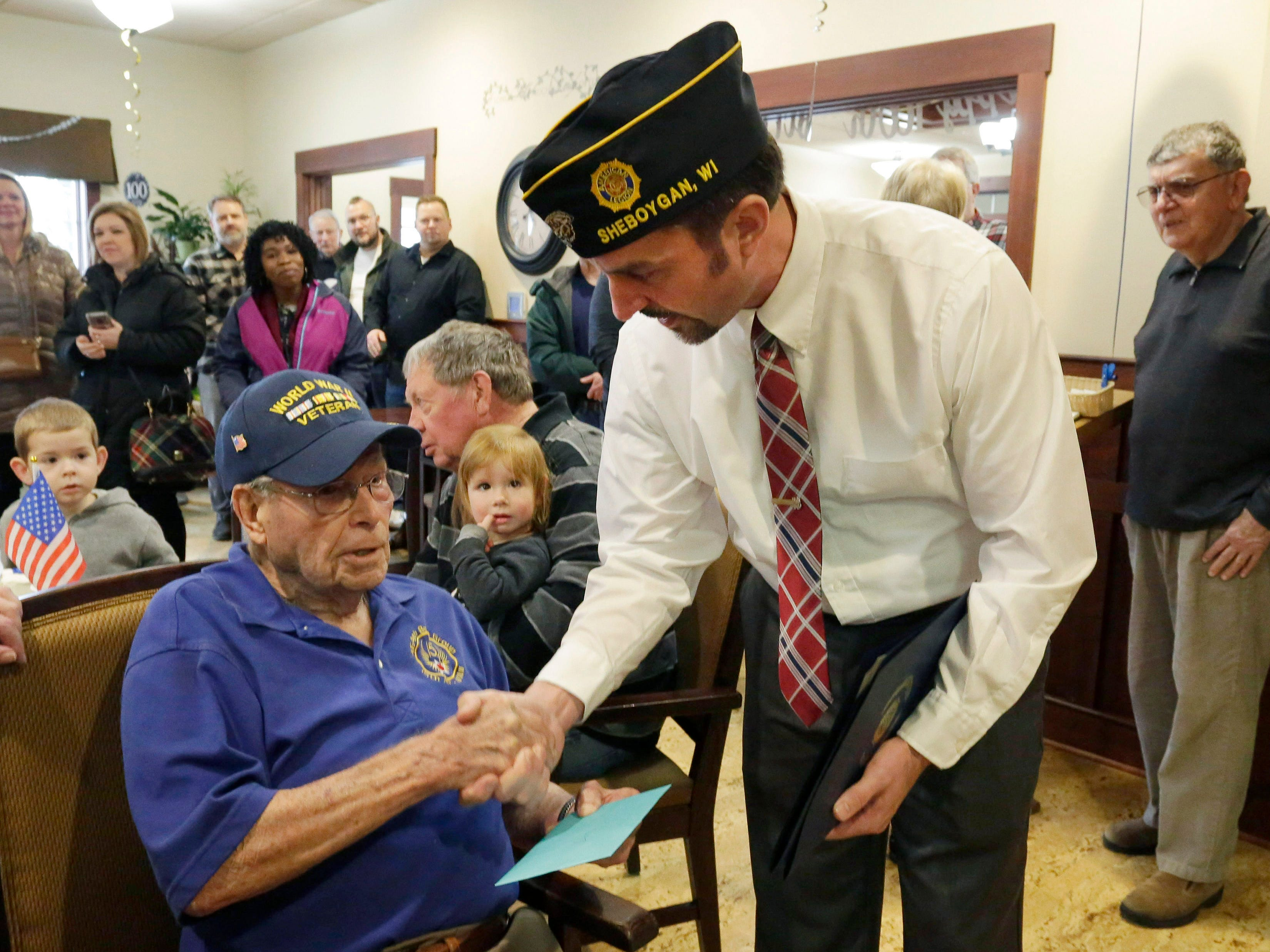 American Legion's Craig Stewart, right, greets World War II veteran Don Harder on his 100th birthday, Friday January 18, 2019, 2019, at Pine Haven Christian Communities in Oostburg, Wis.