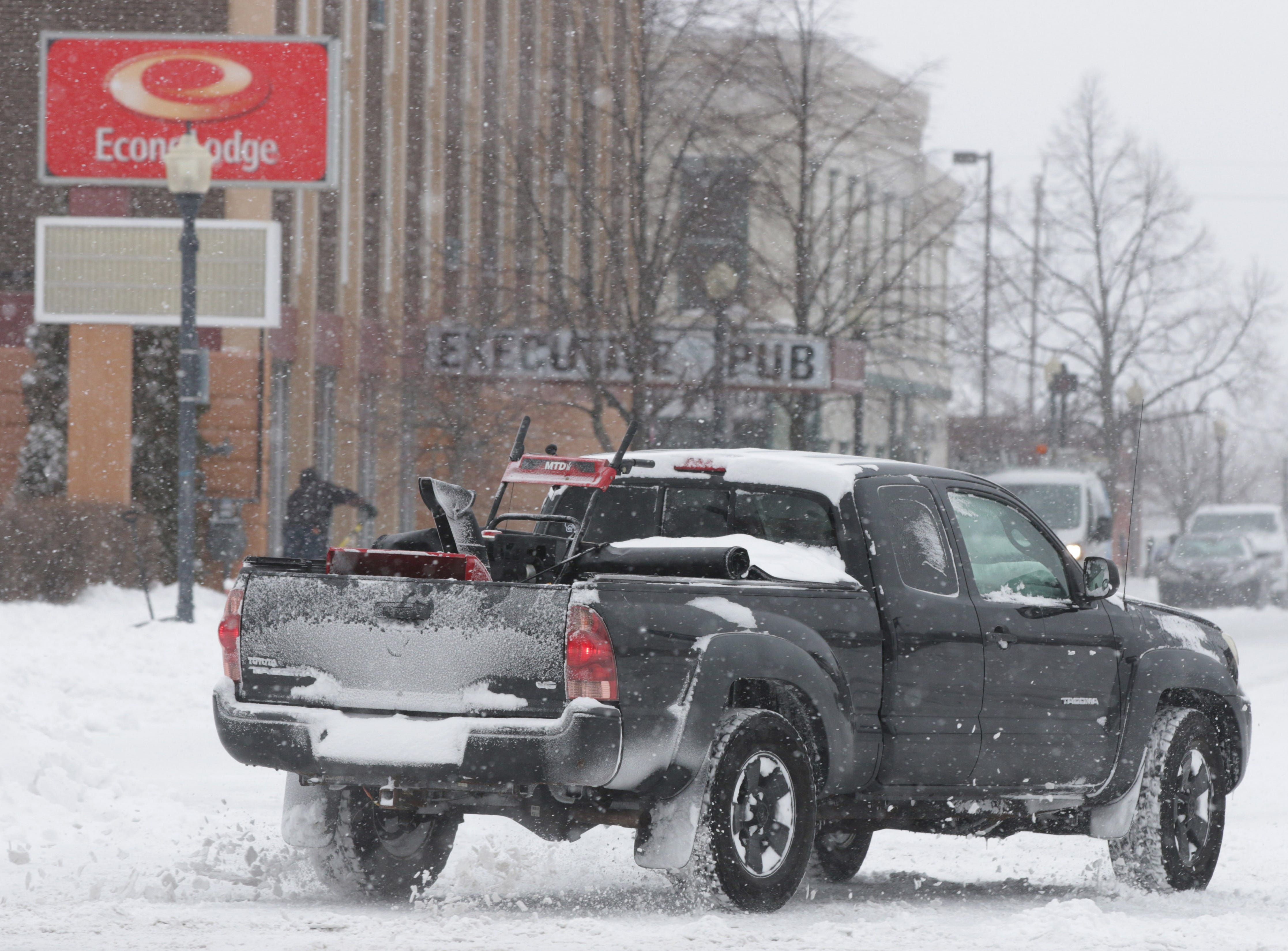 A truck carries a snowblower in its bed, Saturday, January 19, 2019, in Sheboygan, Wis.