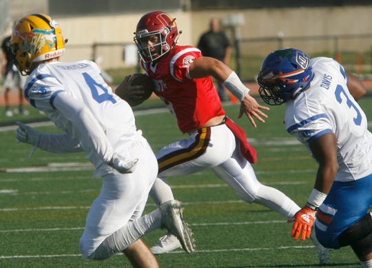 West All-Star quarterback Vincent Walea looks for room to run against East All-Star defenders Bret Schuyler, left, and Nate Davis during the West's 35-24 victory in the 46th annual Ventura County High School All-Star Football Game at Ventura College on Saturday.