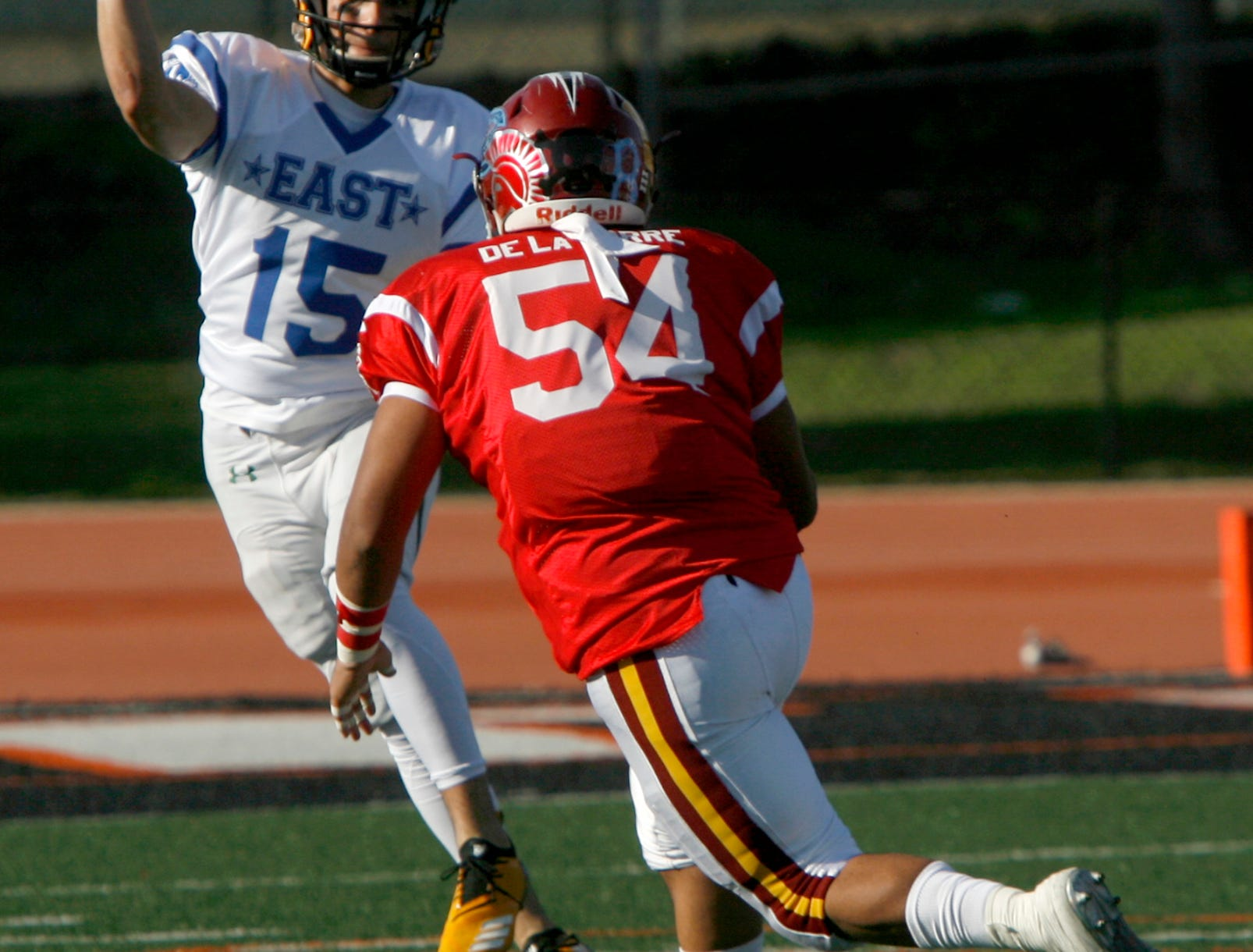 After getting flushed out of the pocket, East All-Star quarterback Steven McDaniel looks to pass on the run as West All-Star defensive lineman Gilbert De La Torre gives chase during the West's 35-24 victory in the 46th annual Ventura County High School All-Star Football Game at Ventura College on Saturday.