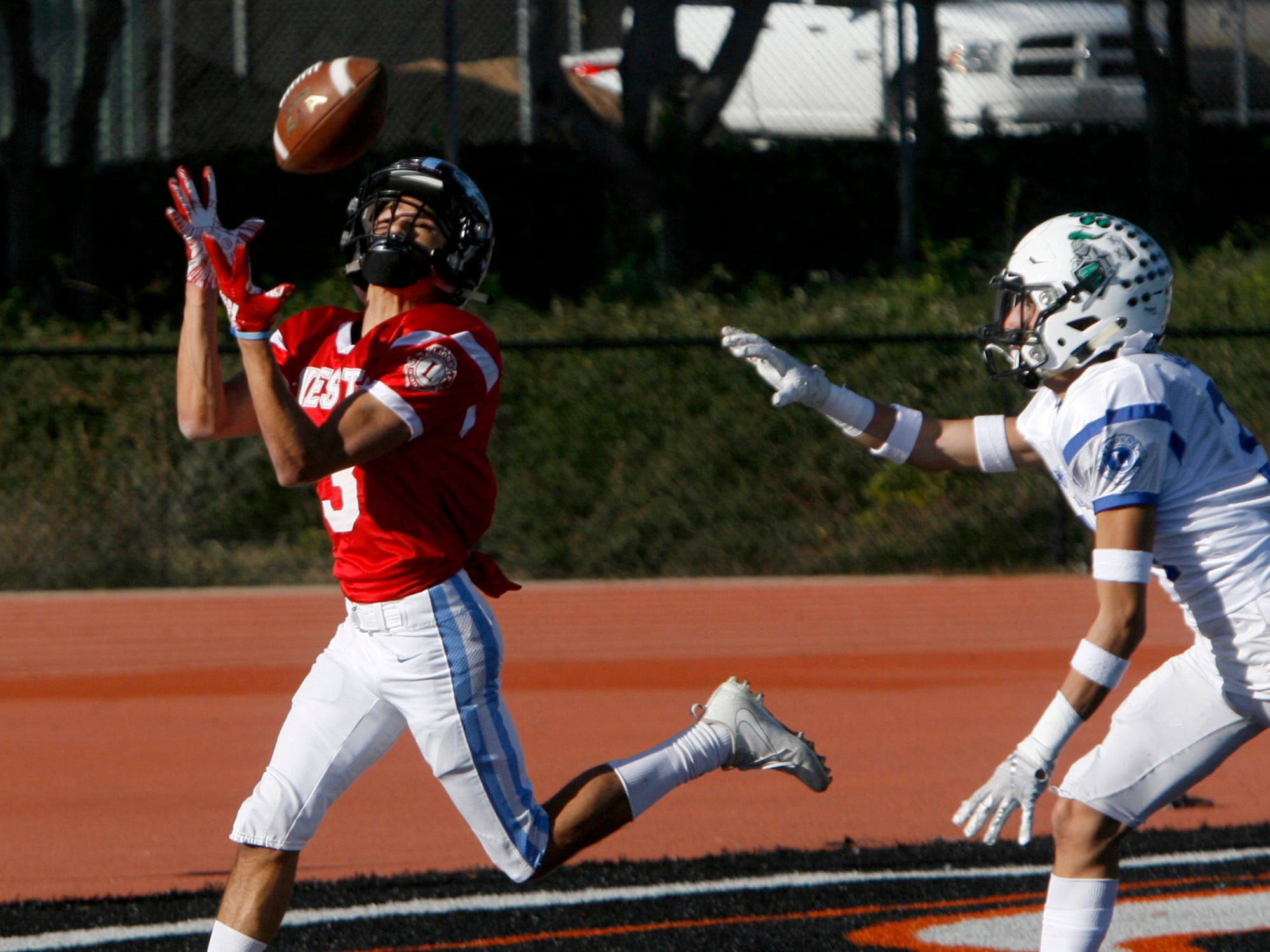 West All-Star wide receiver Devin Morris catches a touchdown pass behind East All-Star defensive back Ryan Vasquez during the West's 35-24 victory in the 46th annual Ventura County High School All-Star Football Game at Ventura College on Saturday.