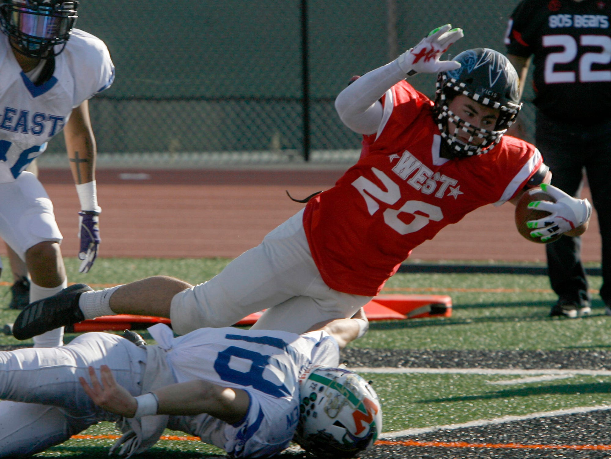 West All-Star running back Noah Conboy dives over East All-Star linebacker Andrew Lichtenstein for a touchdown during the West's 35-24 victory in the 46th annual Ventura County High School All-Star Football Game at Ventura College on Saturday.