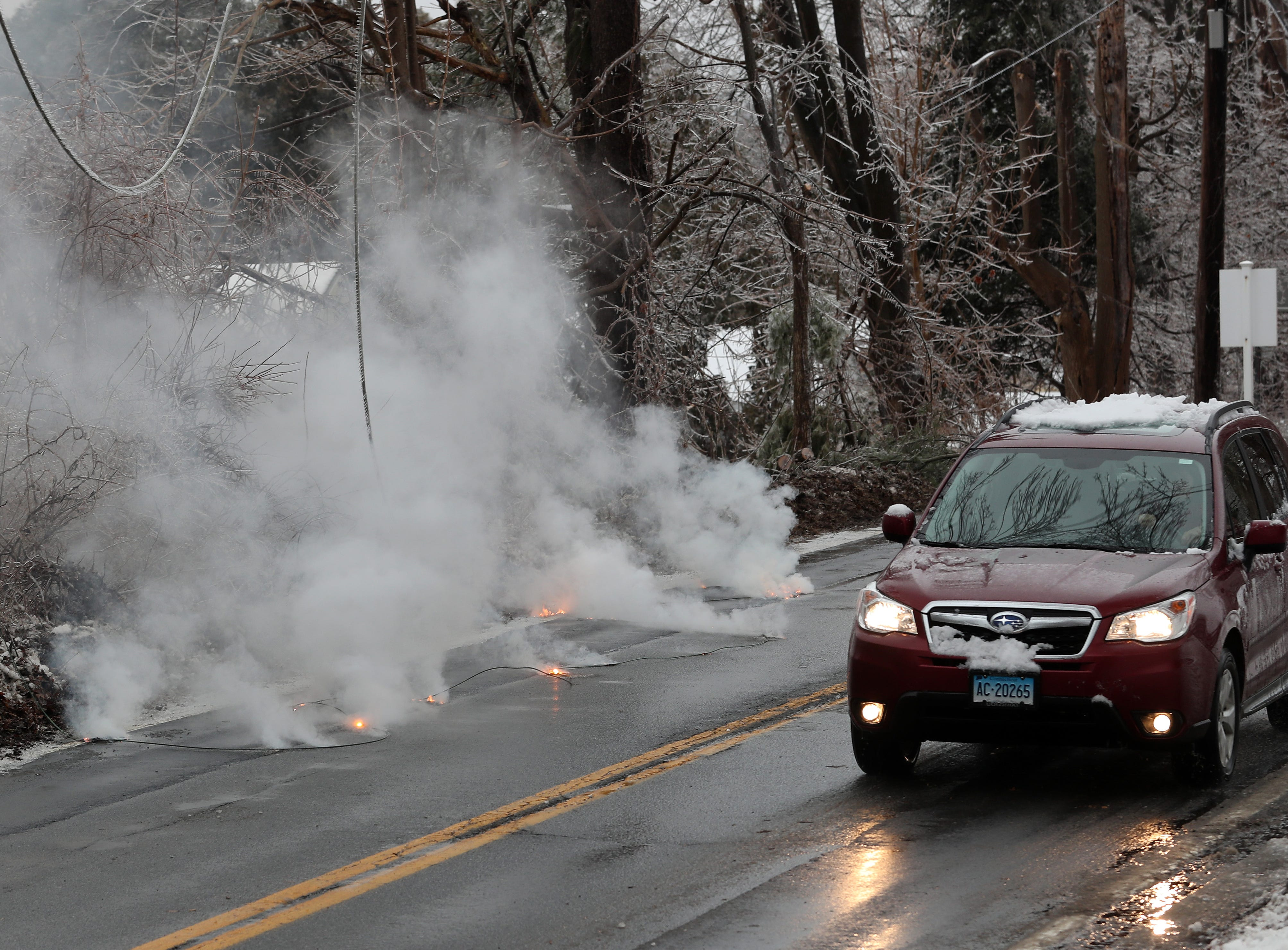 A car drives by burning power lines on the side of Route 121 in North Salem Jan. 20, 2019. A large tree branch came down taking the power lines with it.