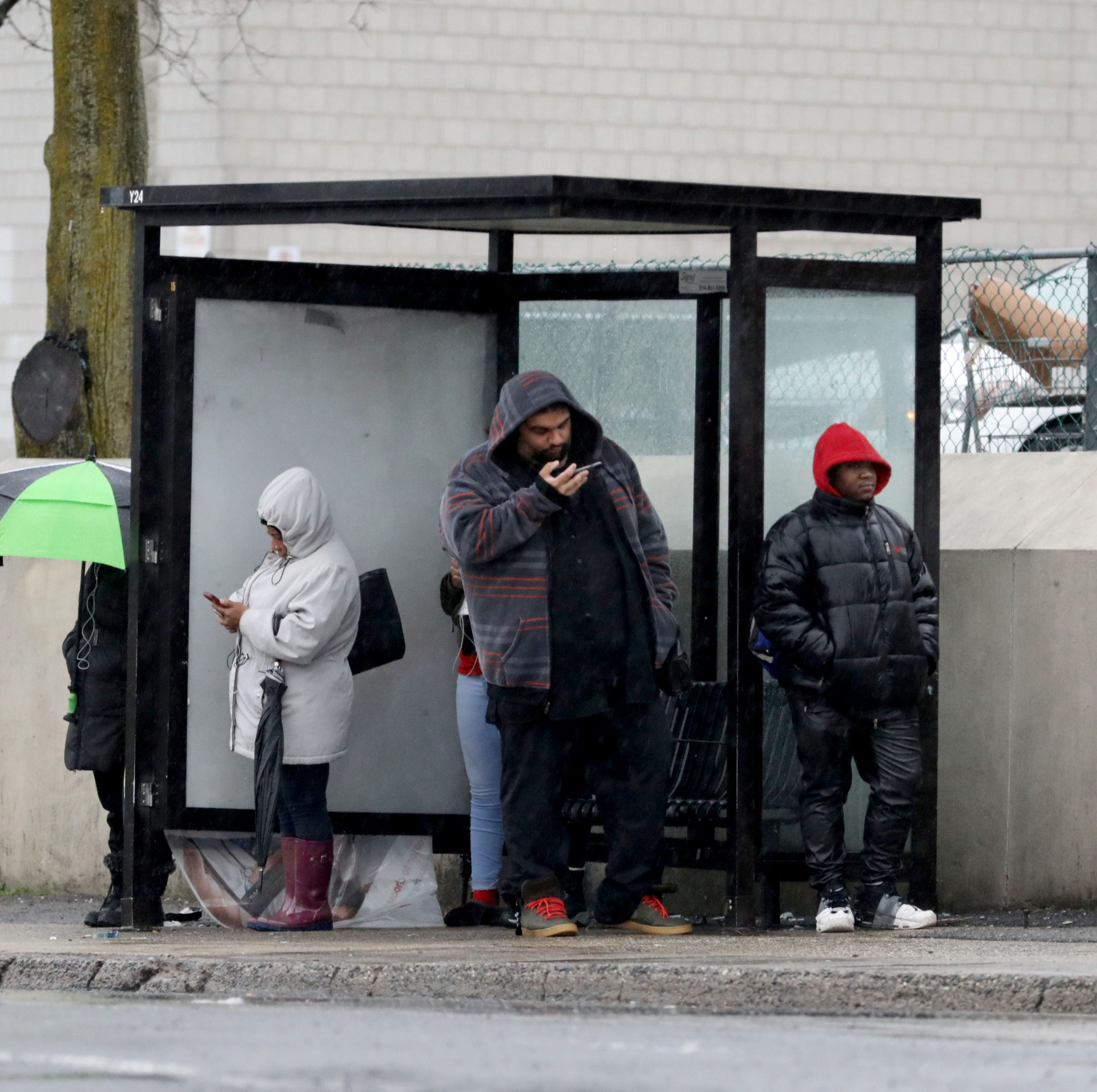 Bus commuters wait for the Bee Line bus as they stand in a bus shelter with umbrellas, on Central Park Avenue and McLean Avenue in Yonkers, Jan. 20, 2019. Southern Westchester experienced more rain than snow in this latest snowstorm.