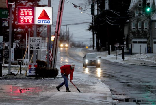 A gas station employee cleared the sidewalk on route 9 in Ossining Jan. 20, 2019. Snow gave way to rain overnight. Temperatures are expected to drop throughout the day, leaving icy conditions throughout the region.