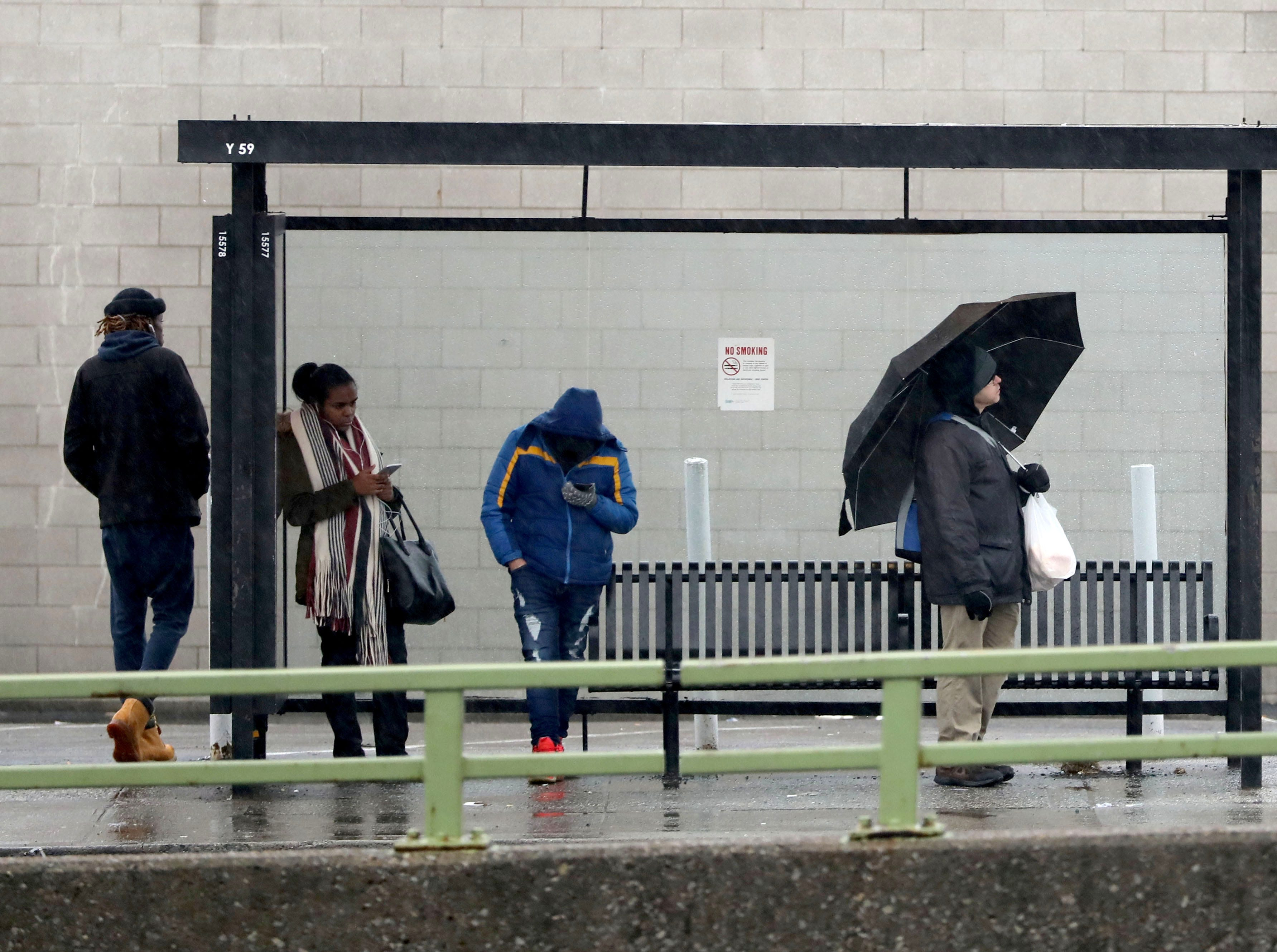 Bus commuters wait for the Bee Line bus as they stand in a bus shelter with umbrellas, on Central Park Avenue and Yonkers Avenue in Yonkers, Jan. 20, 2019. Southern Westchester experienced more rain than snow in this latest snowstorm.