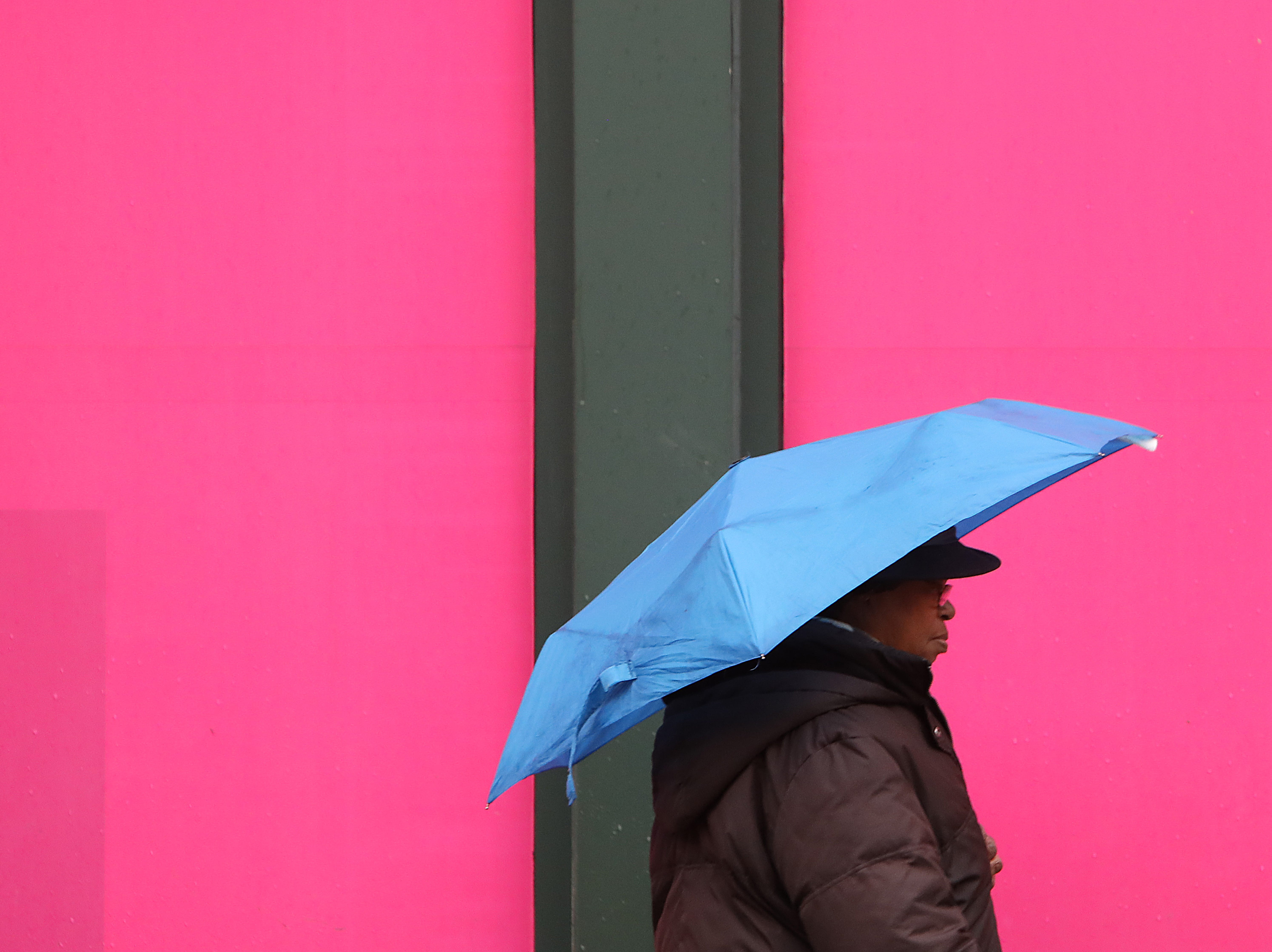 A woman shielding herself from rain passes a T-Mobile store in White Plains Jan. 20, 2019. Snow turned to sleet or heavy rain overnight and will continue throughout the day. Colder temperatures are expected later in the day which will cause a flash freeze throughout the region.