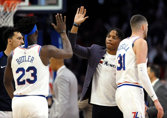 Philadelphia 76ers' Markelle Fultz, second from right, greets Jimmy Butler (23) and Mike Muscala (31) during a timeout in the second half of the team's NBA basketball game against the Oklahoma City Thunder last month. Fultz hasn't played since Nov. 19.