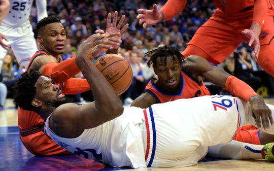 Philadelphia 76ers' Joel Embiid (21) grabs a loose ball next to Oklahoma City Thunder's Russell Westbrook, back left, and Jerami Grant during the second half of an NBA basketball game Saturday, Jan. 19, 2019, in Philadelphia. The Thunder beat the 76ers 117-115. (AP Photo/Michael Perez)