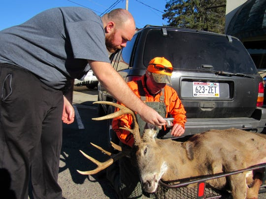 FILE - In this Nov. 21, 2016 file photo, Daniel Crook, right, looks at a photo Dan Ruhland took of Crook's nine point deer  in downtown Plain, Wis. The Wisconsin Conservation Congress plans to ask outdoor lovers whether the state should again offer bounties for deer infected with chronic wasting disease. The congress plans to put the question to attendees at its statewide spring hearings in April 2019.