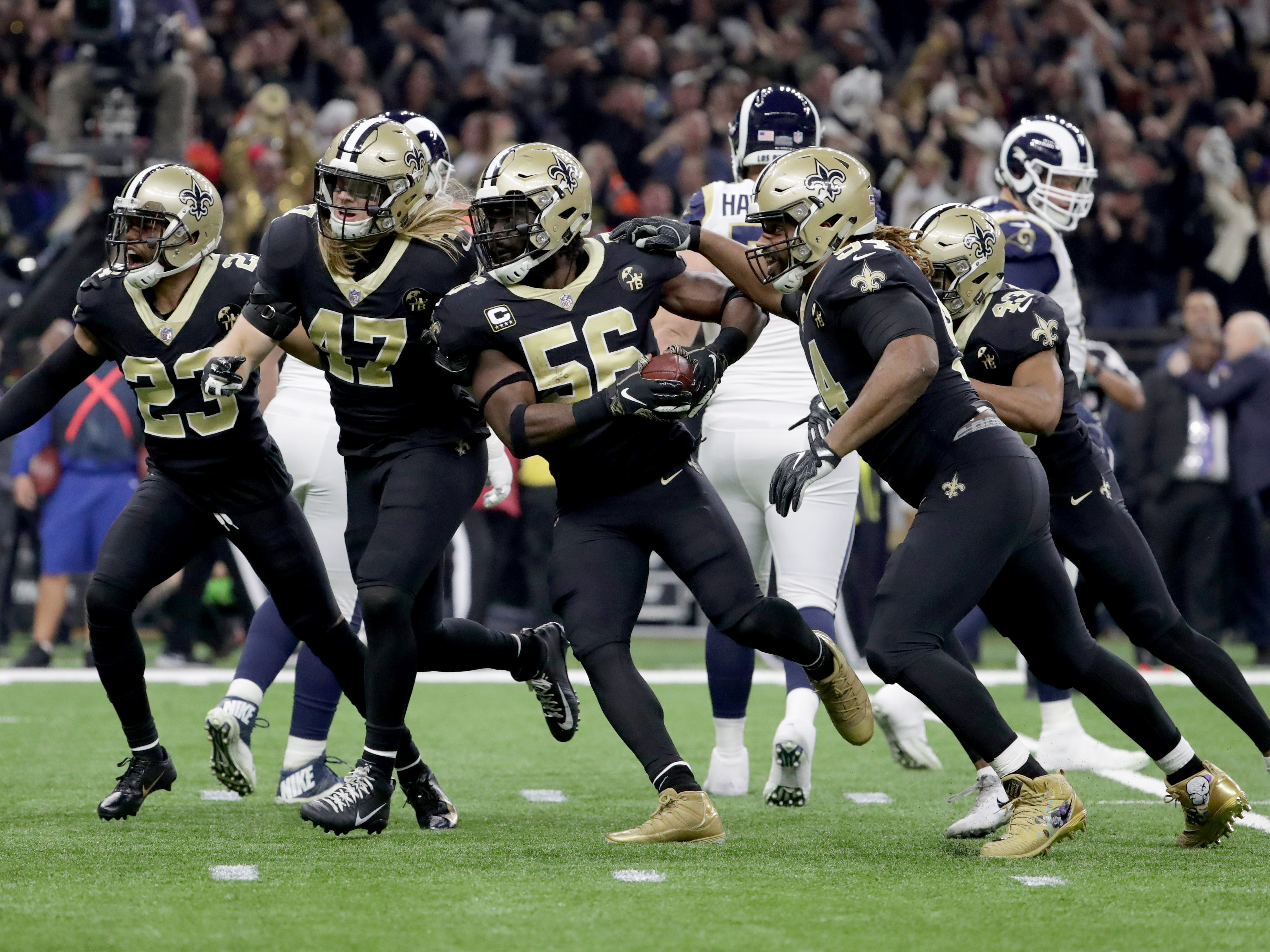 New Orleans Saints outside linebacker Demario Davis (56) celebrates with teammates after intercepting a pass against the Los Angeles Rams during the first quarter of the NFC Championship game at Mercedes-Benz Superdome.