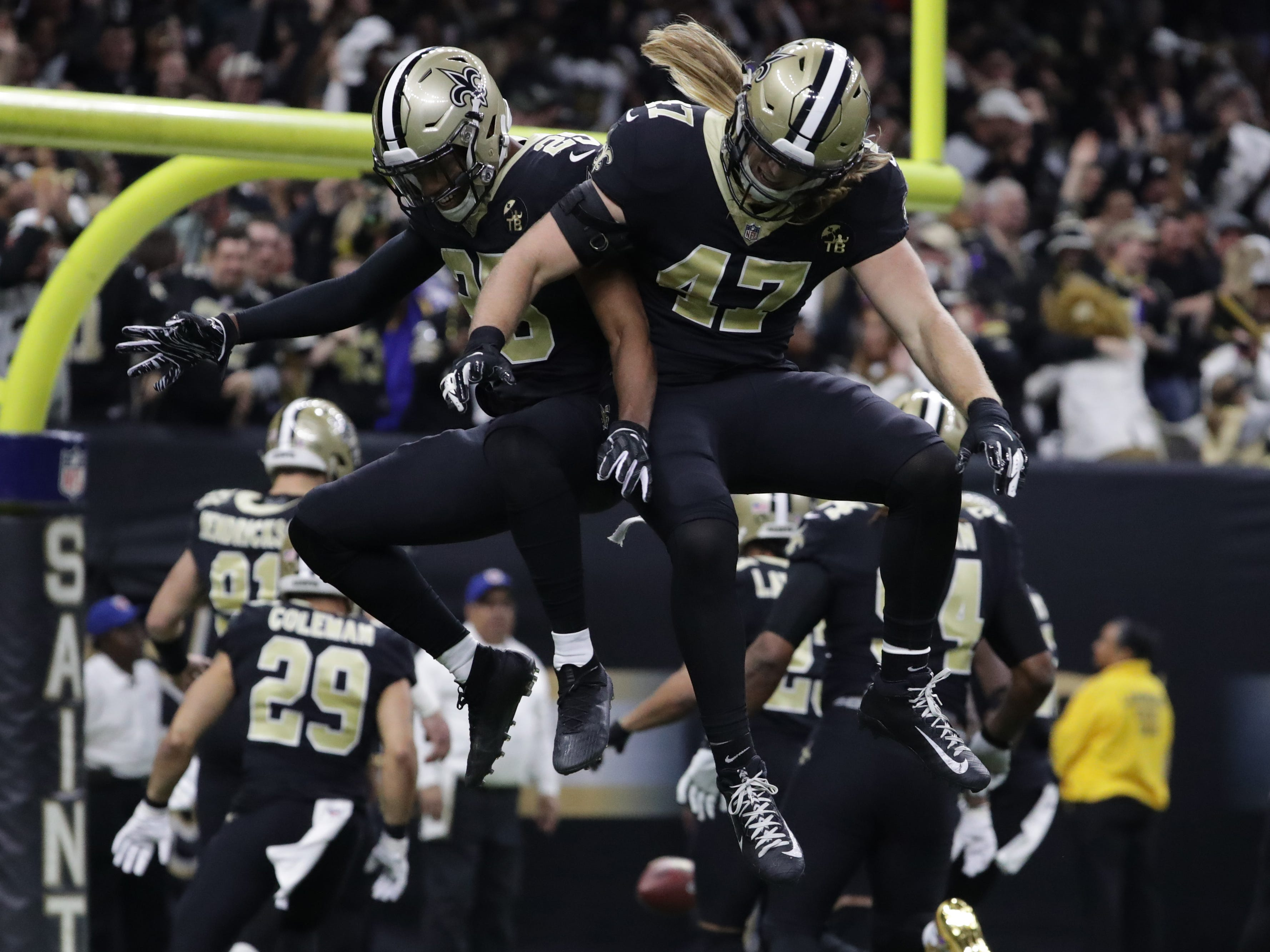 New Orleans Saints cornerback Eli Apple (25) and middle linebacker Alex Anzalone (47) celebrate after a turnover against the Los Angeles Rams during the first quarter of the NFC Championship game at Mercedes-Benz Superdome.