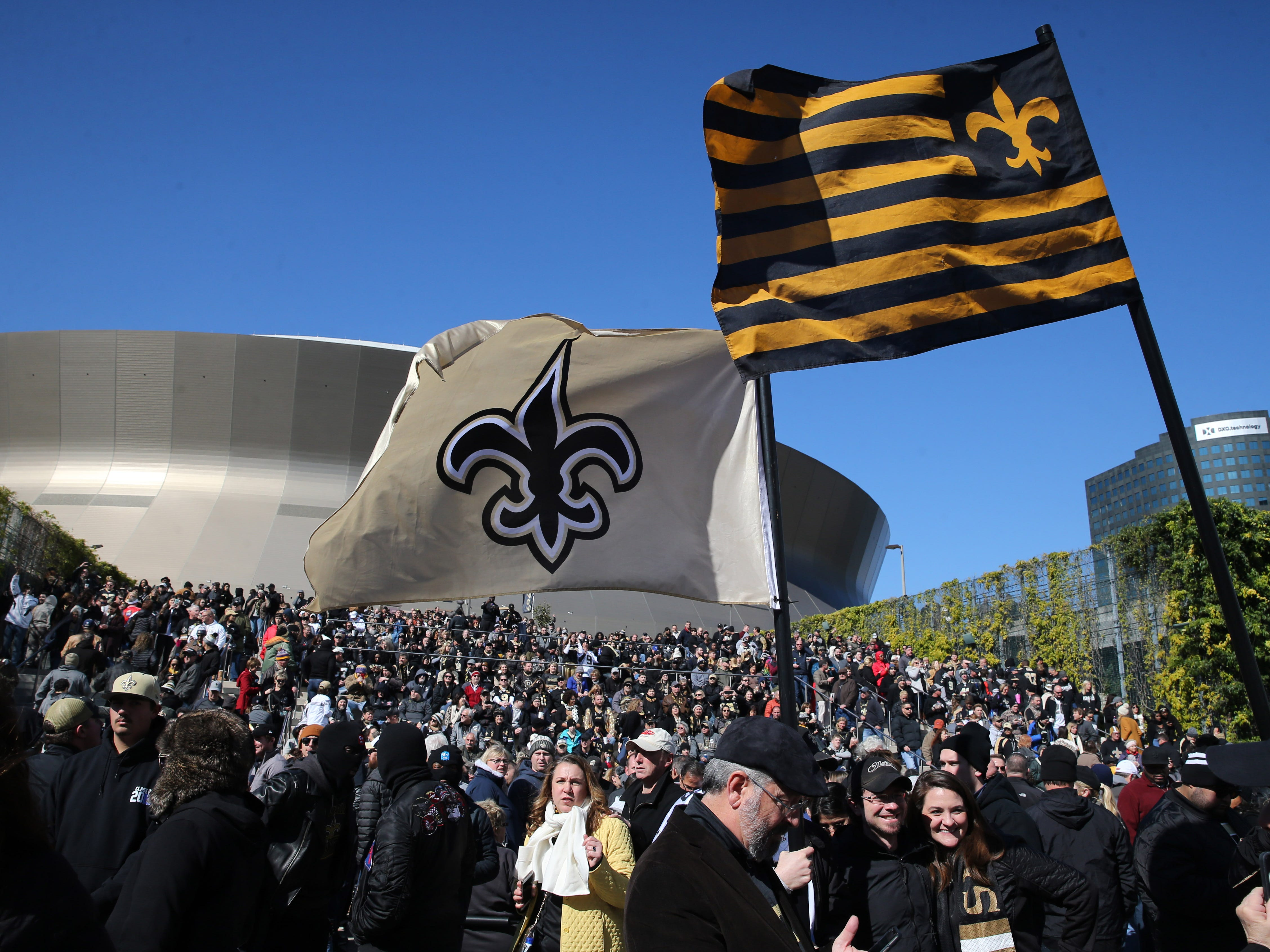 New Orleans Saints fans wave flags outside the Mercedes-Benz Superdome before the NFC Championship game between the Saints and the Los Angeles Rams.