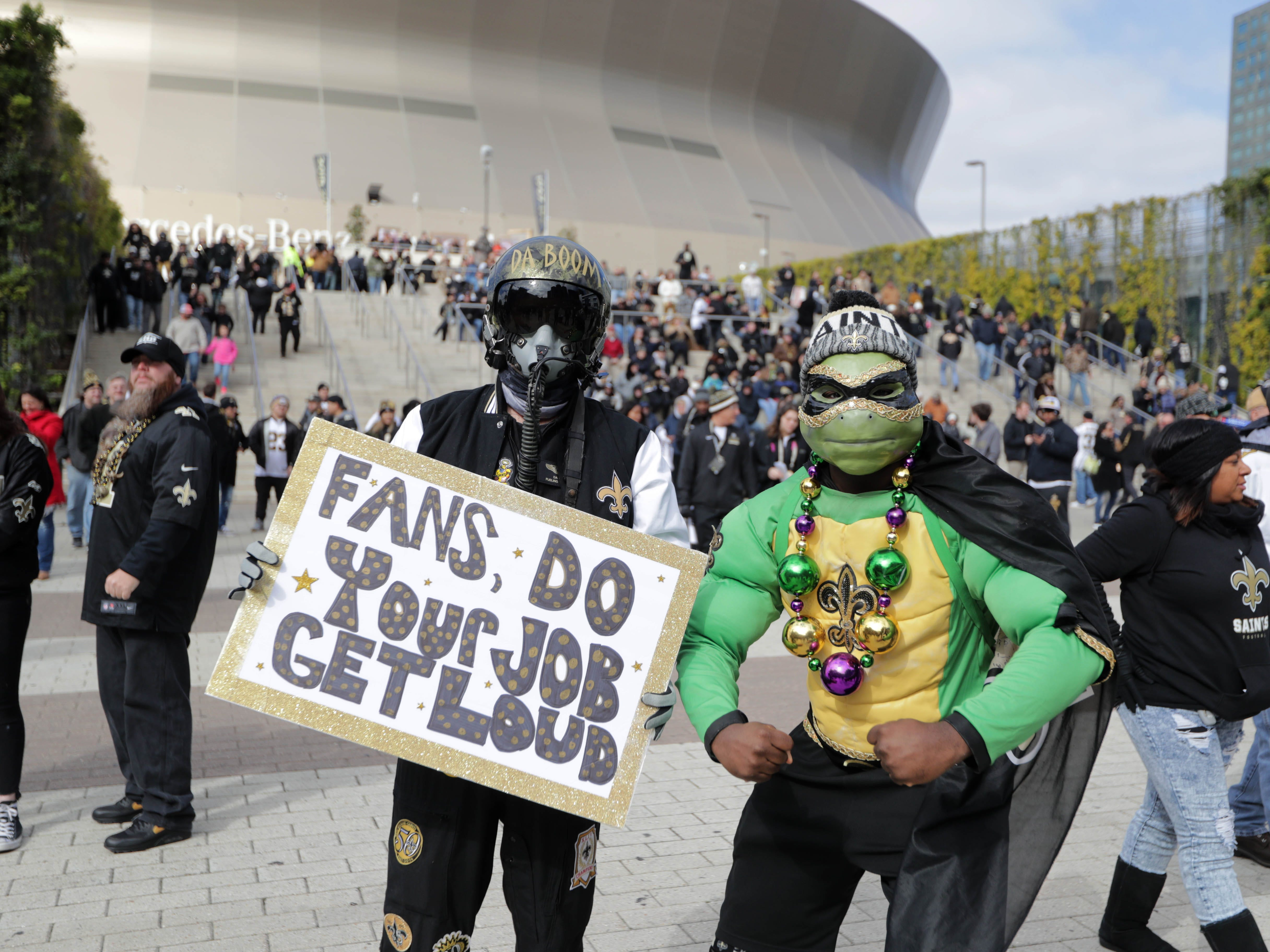 New Orleans Saints fans pose outside the Mercedes-Benz Superdome before the NFC Championship game between the Saints and the Los Angeles Rams.