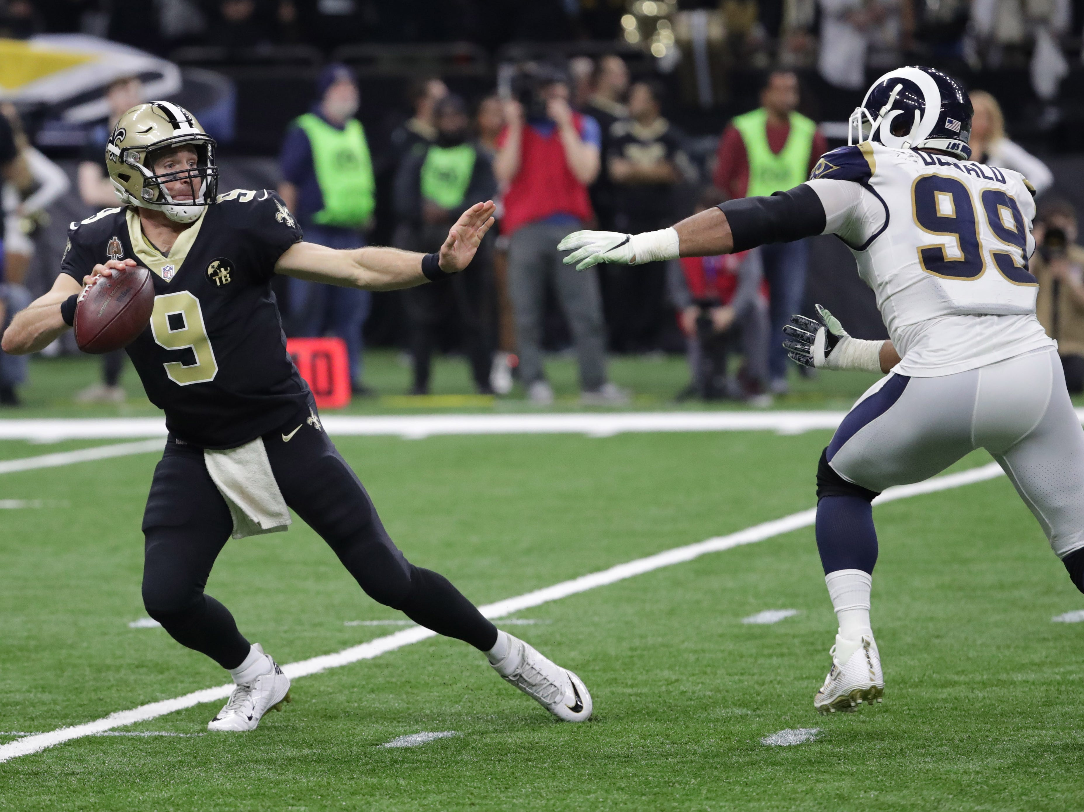 New Orleans Saints quarterback Drew Brees (9) is pressured by Los Angeles Rams defensive end Aaron Donald (99) during the second quarter the NFC Championship game at Mercedes-Benz Superdome.