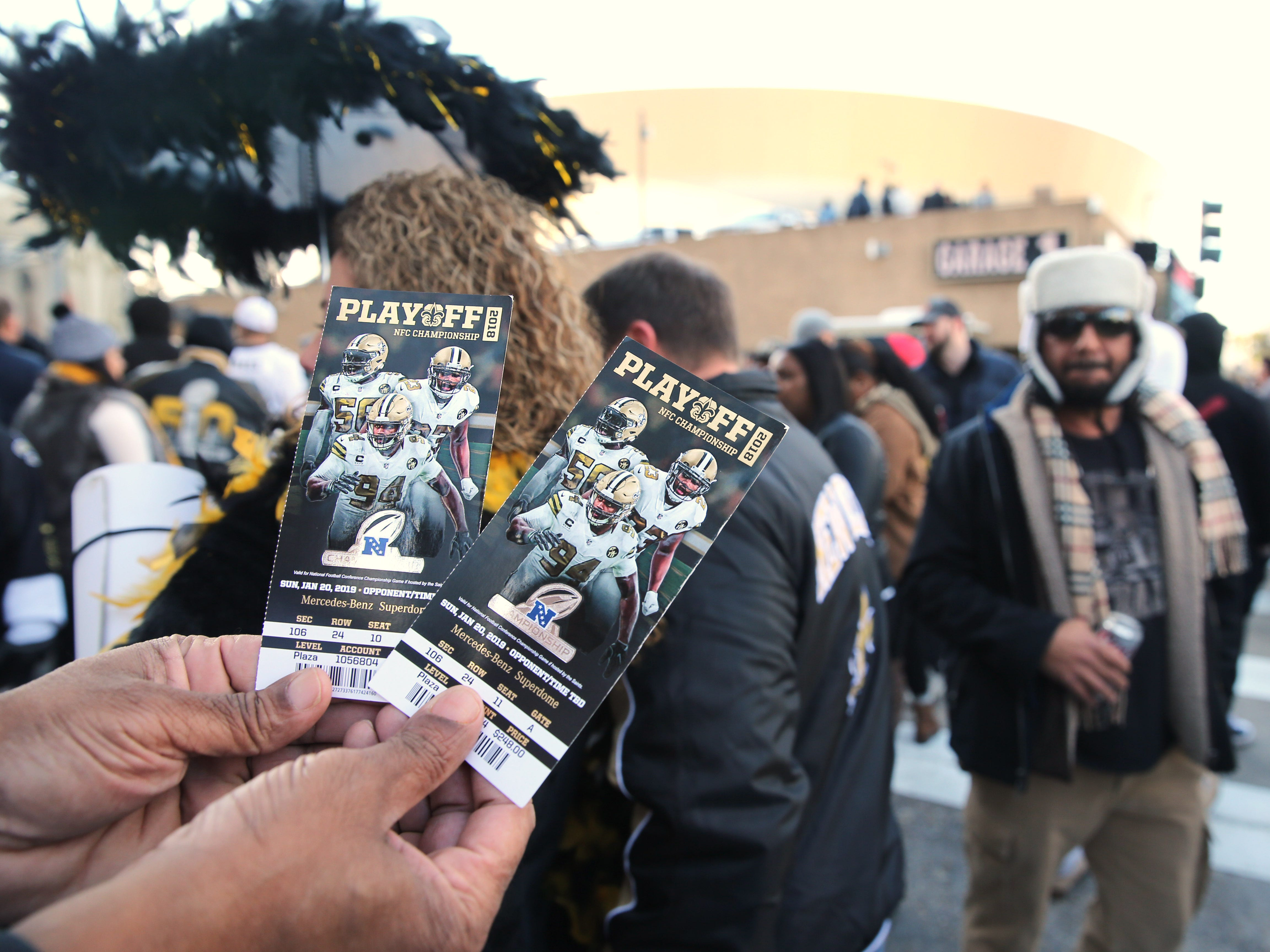 A fan displays tickets for the NFC Championship game between the New Orleans Saints and the Los Angeles Rams at Mercedes-Benz Superdome.