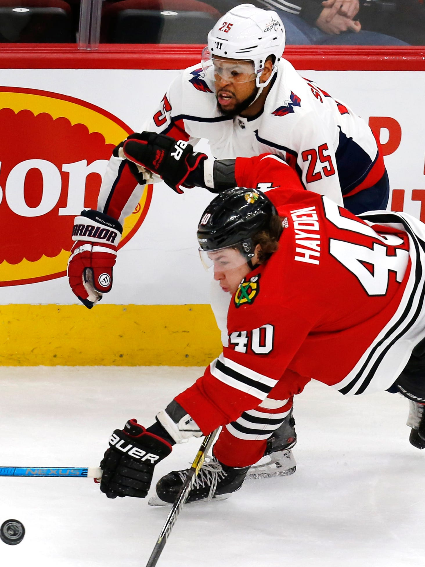 Washington Capitals right wing Devante Smith-Pelly, top, and Chicago Blackhawks right wing John Hayden reach for the puck in Sunday's game in Chicago.