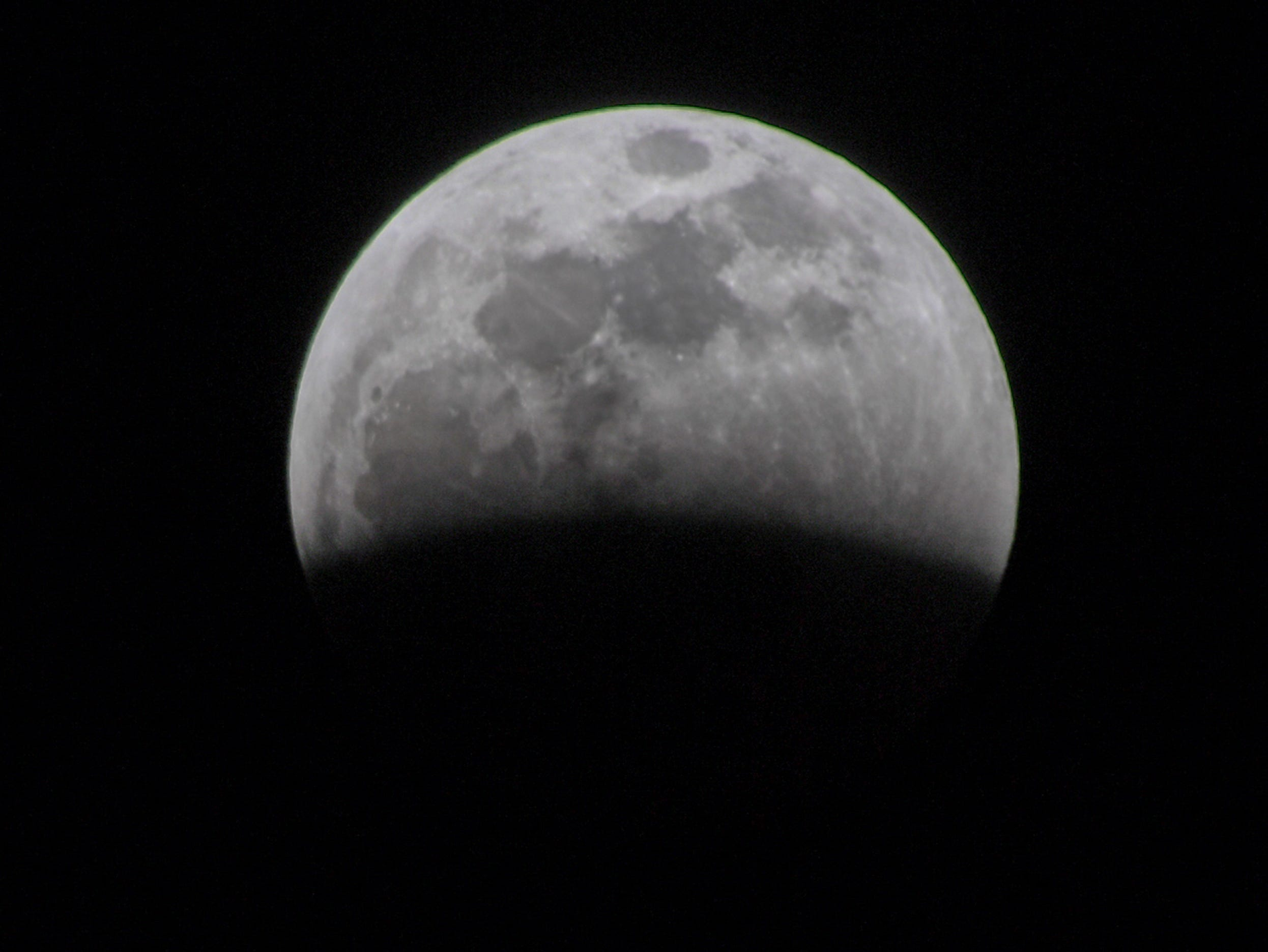 The early stage of the Super blood wolf moon total lunar eclipse, at 10:59 p.m. (EST) January 20, 2019, when the moon began edging into Earth's shadow and became darkened at 11:41 p.m., seen from Anderson, S.C.