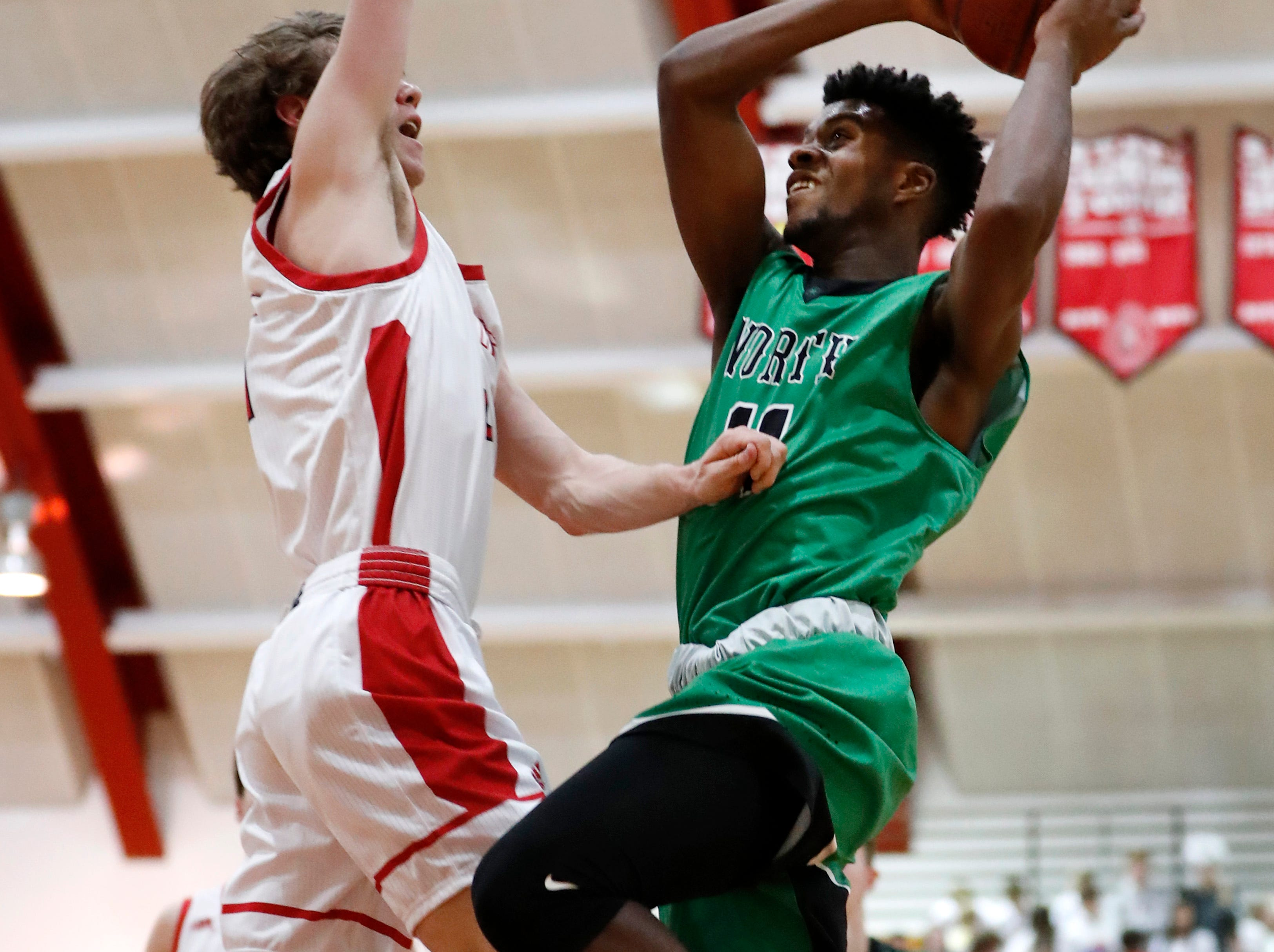 Oshkosh North High SchoolÕs Abraham Schiek goes for a layup while covered by Neenah High SchoolÕs Bryce Henderson Friday, Jan. 18, 2019, in Neenah, Wis. Oshkosh North High School defeated Neenah High School 63-60.
