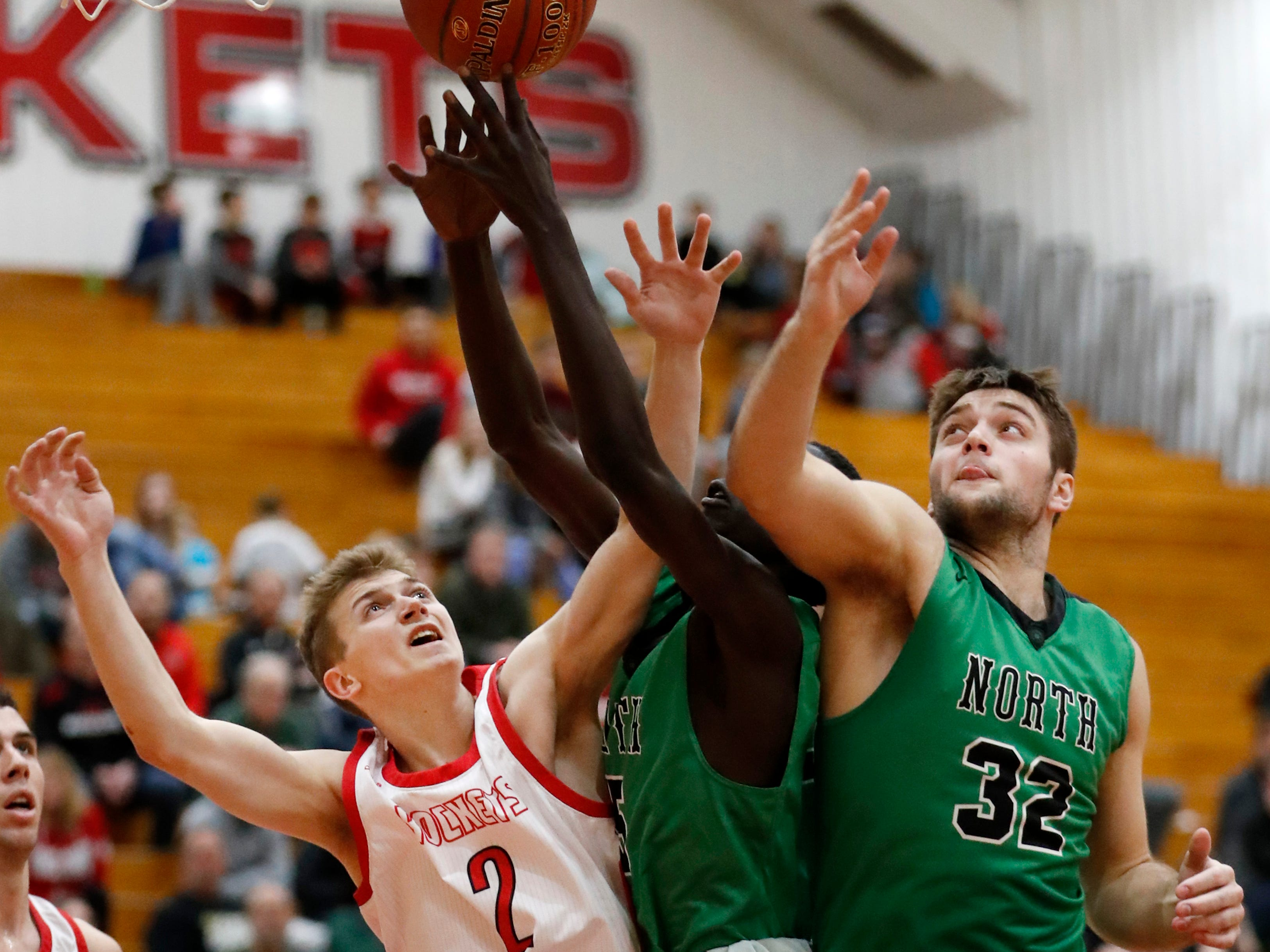 Neenah High SchoolÕs Jake Hablewitz, Oshkosh North High SchoolÕs Garang Deng and Oshkosh North High School's Matt Hickey go for a rebound Friday, Jan. 18, 2019, in Neenah, Wis.