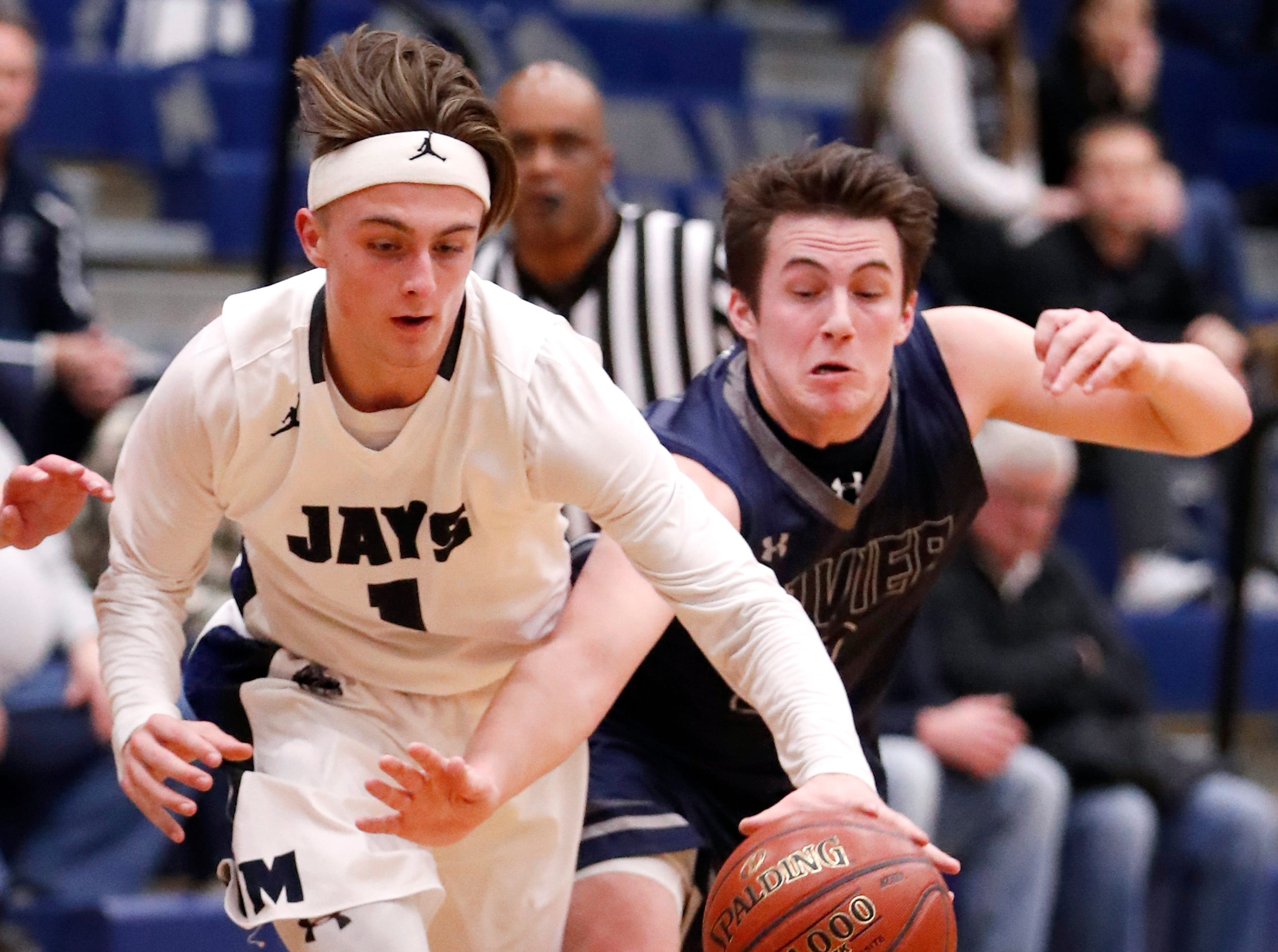 Menasha High SchoolÕs Jay Pawlowski and Xavier High SchoolÕs Henry Egan work to gain control of the ball Thursday, Jan. 17, 2019, in Menasha, Wis. Xavier High School defeated Menasha High School 71-61.