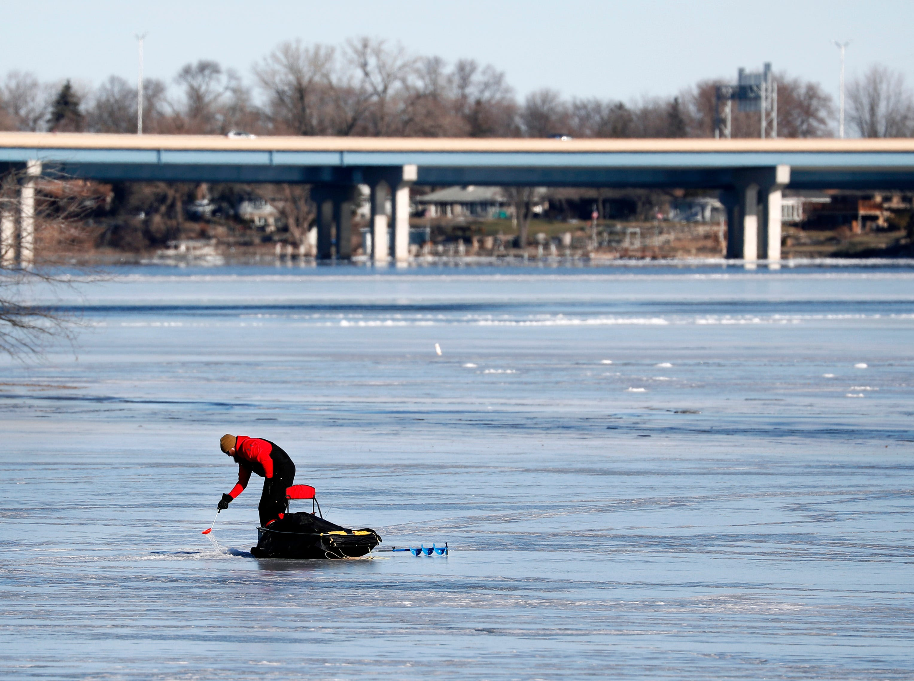 Mark Taczala, of Menasha, skims the loose ice away from an ice fishing hole Wednesday, Jan. 16, 2019, in Menasha, Wis.