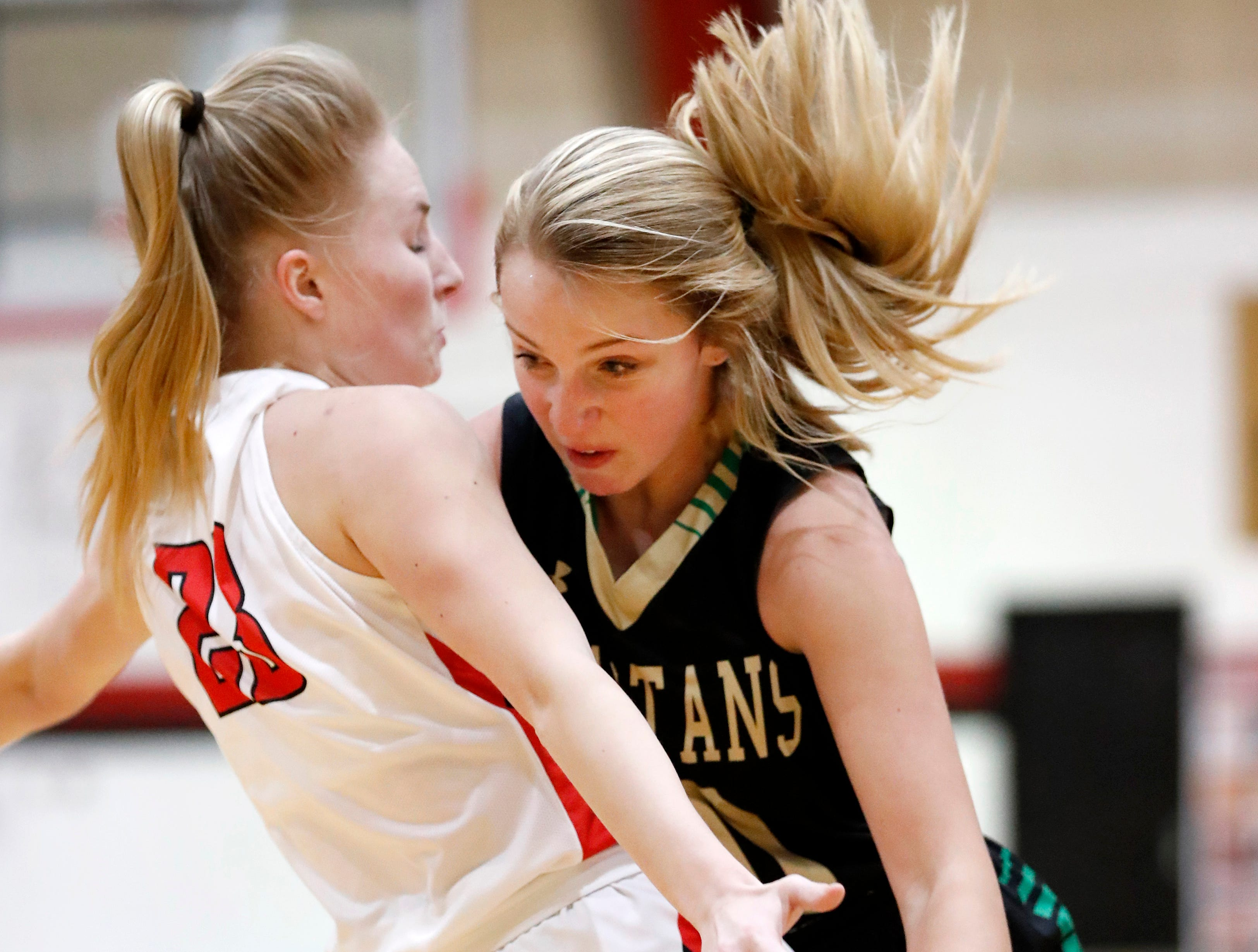 Neenah High SchoolÕs Ella Schroeder fouls Oshkosh North High SchoolÕs Brooke Ellestad as she drives to the basket Friday, Jan. 18, 2019, in Neenah, Wis.