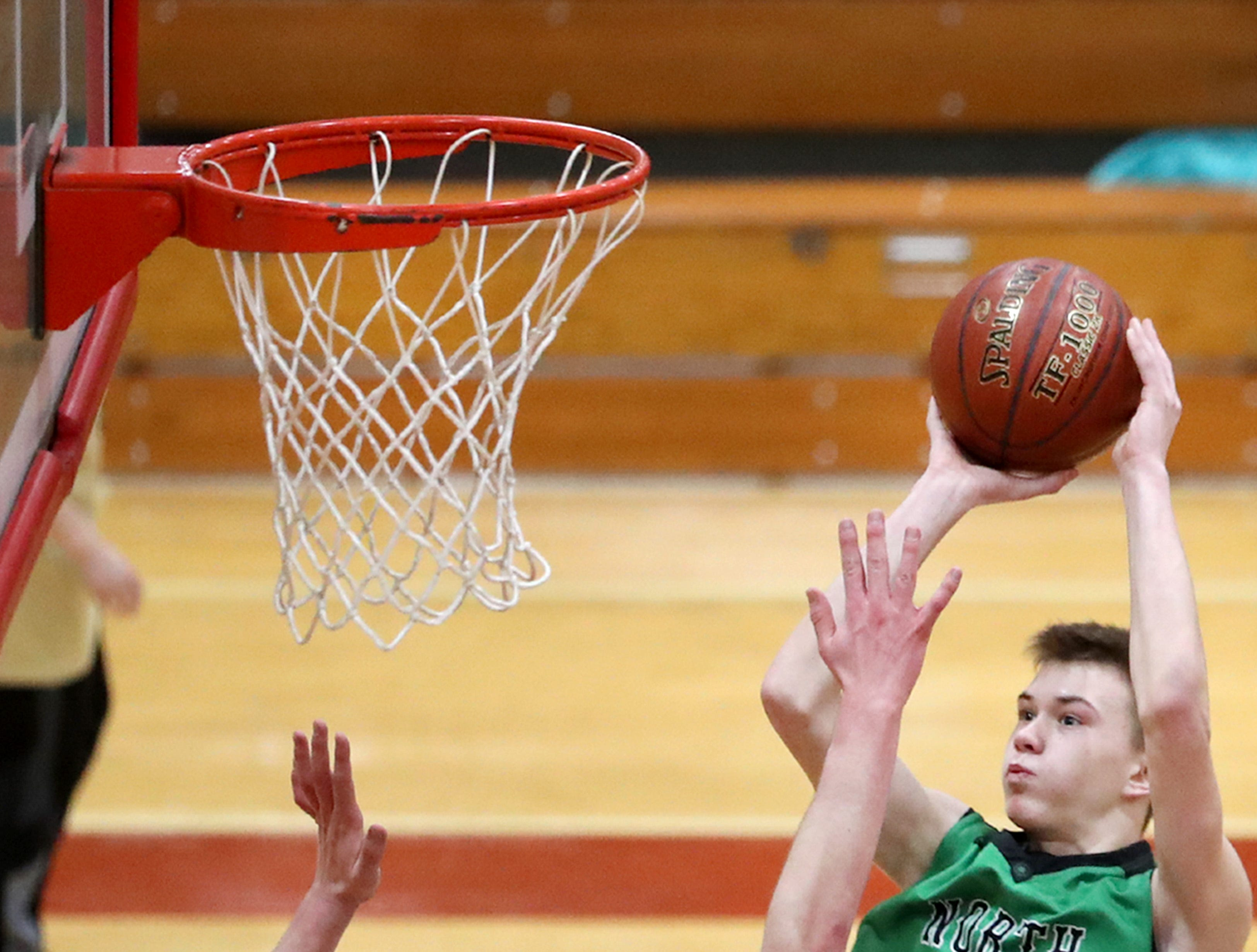 Oshkosh North High SchoolÕs Brennon Colburn takes a shot at the basket while being covered by Neenah High SchoolÕs Ethan Parker Friday, Jan. 18, 2019, in Neenah, Wis. Oshkosh North High School defeated Neenah High School 63-60.