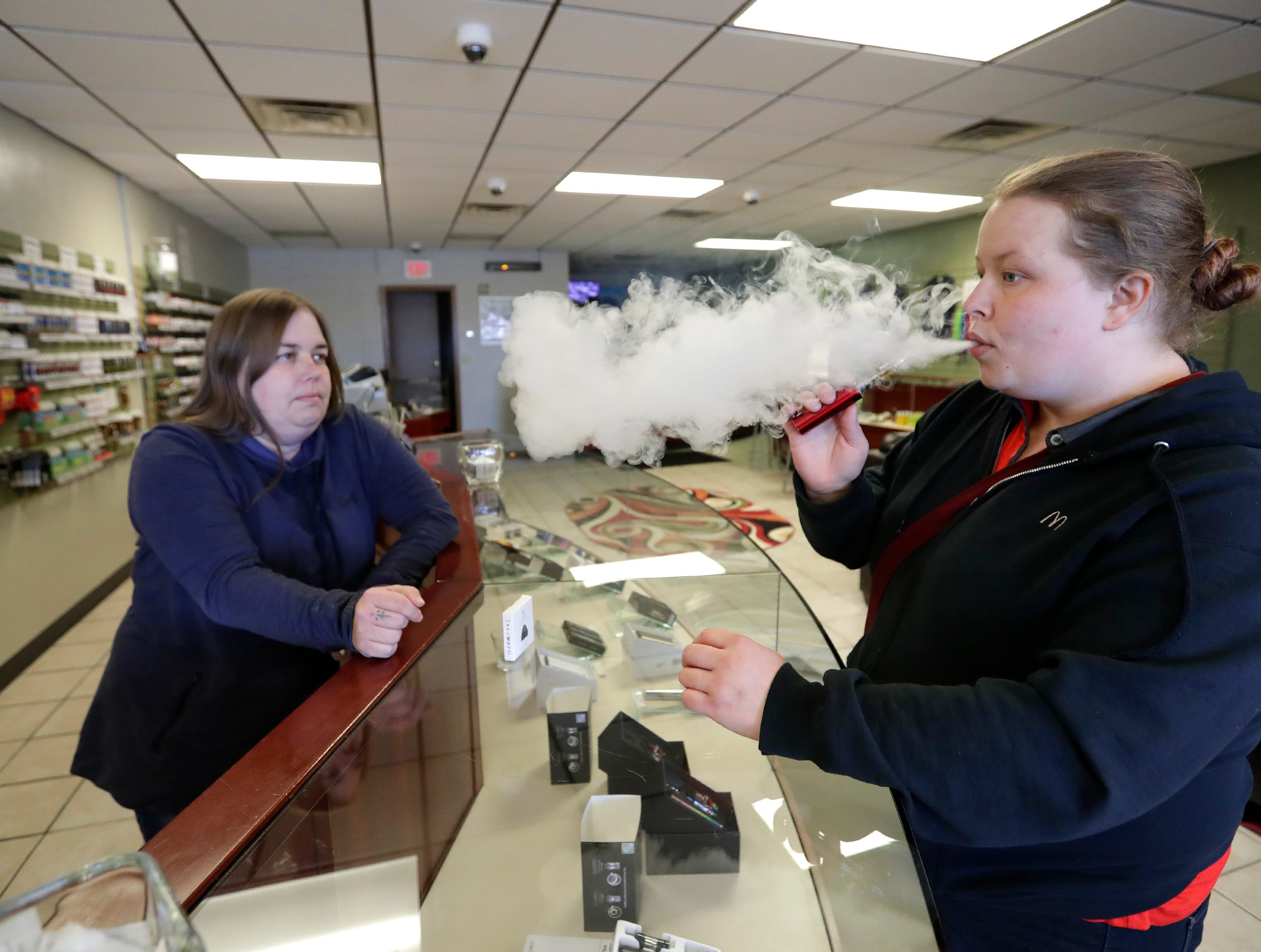 Co-owner Beth Kempen, left, assists Amber Velpel of Appleton as she tries different e-liquid samples for her vape MOD at EVapor of Appleton Wednesday, January 16, 2019, in Appleton, Wis. Kempen owns the shop with her husband Ken Kempen.