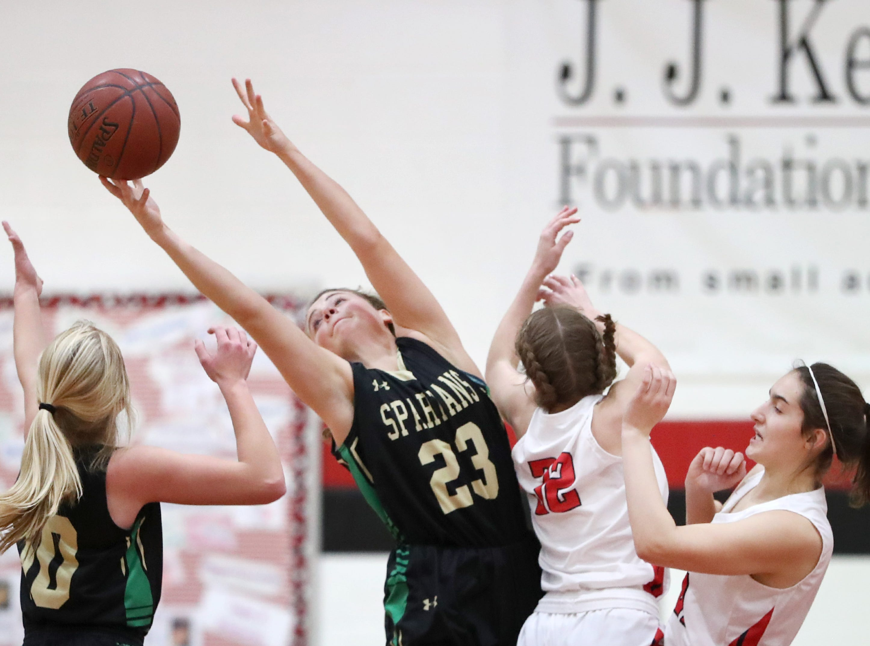 Oshkosh North High SchoolÕs Elle Lieder stretches for a rebound during their game against Neenah High School Friday, Jan. 18, 2019, in Neenah, Wis.