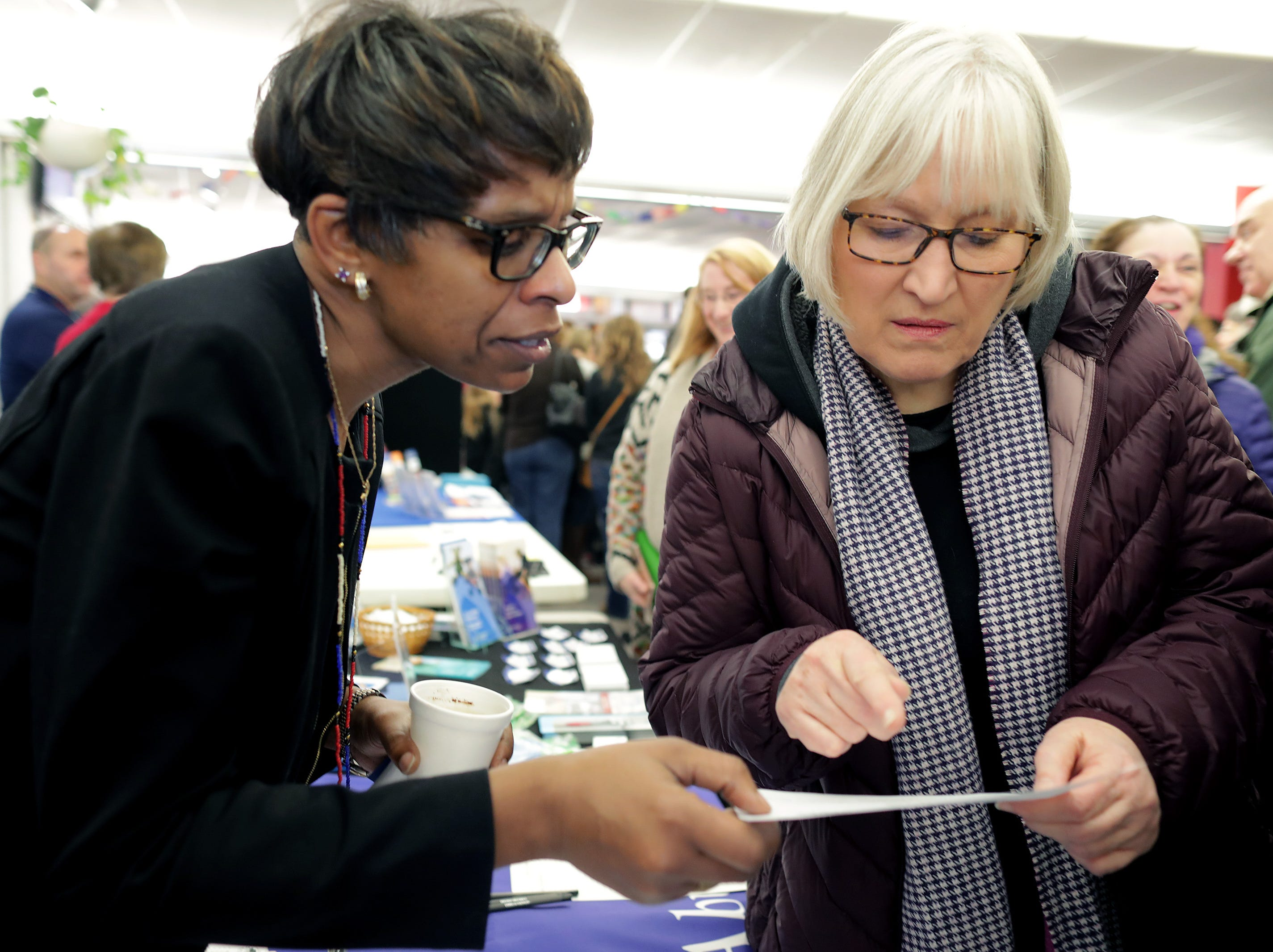 B.A.B.E.S. Inc. Child Abuse Prevention Program Pastor Mahnie Williams shares information with Barb Spaude duriong the first annual MLK Community Day of Service celebration on Monday, January 21, 2019, at Appleton East High School in Appleton, Wis.