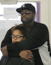 A father holds his daughter as they watch a performance as part of the MLK Community Day of Service in Appleton on Monday.