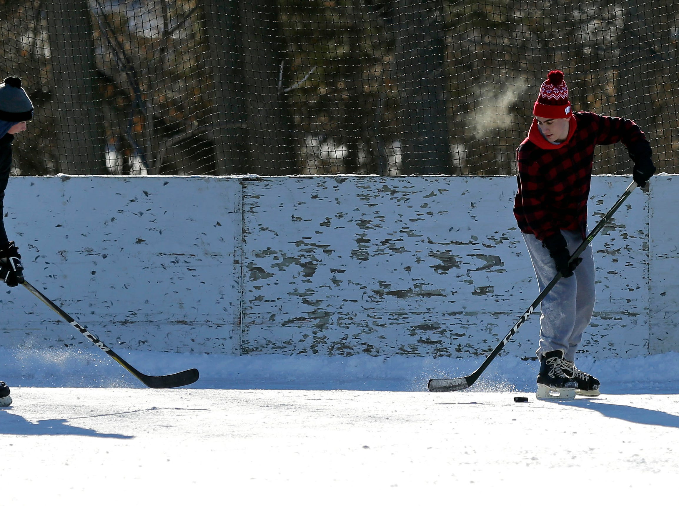 Friends from Neenah gathered for a frigid hockey game Sunday, January 20, 2019, at Pierce Park in Appleton, Wis.