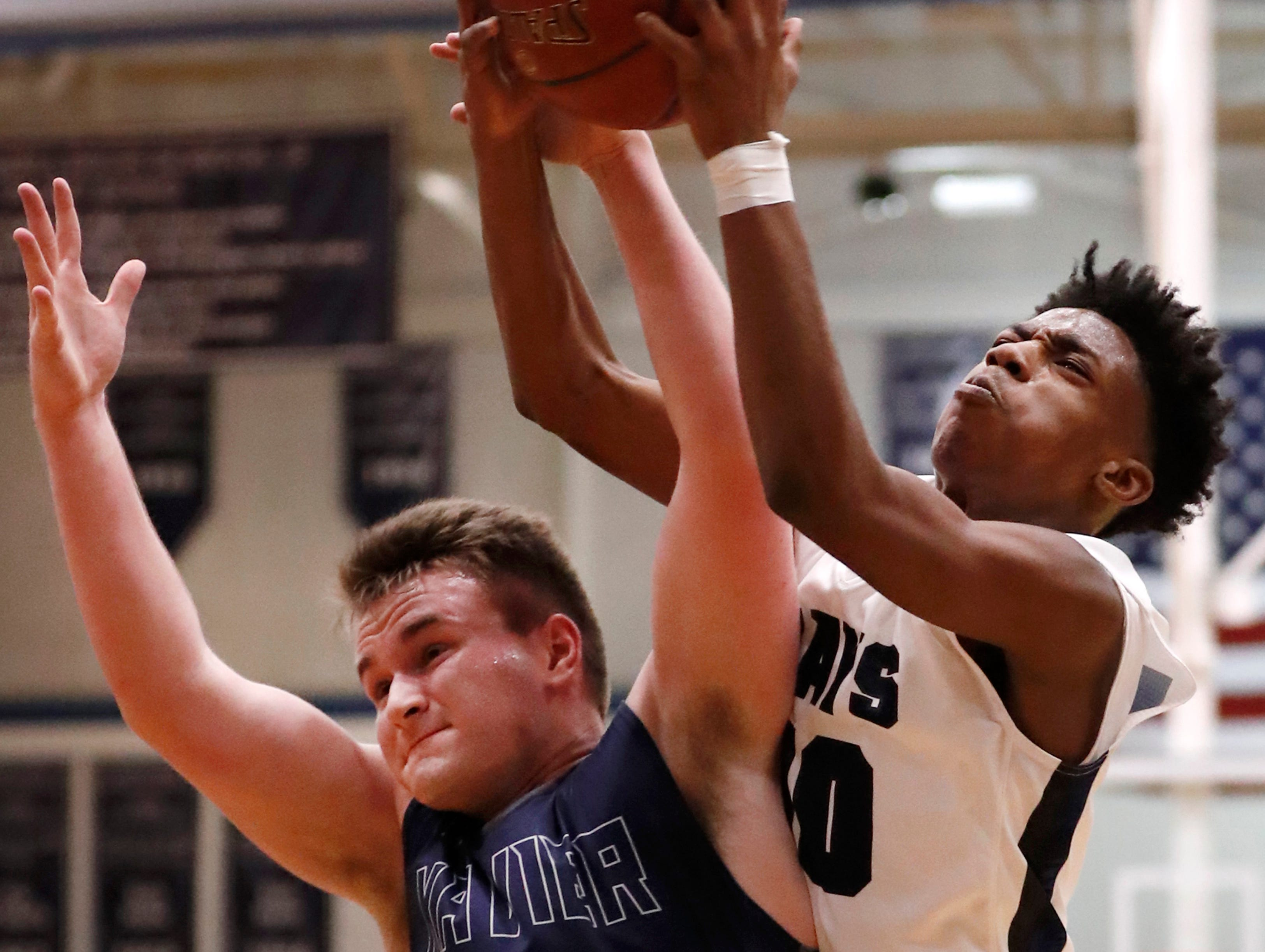 Menasha High SchoolÕs Jalen Womack tries to get a rebound away from Xavier High SchoolÕs Aaron Collins Thursday, Jan. 17, 2019, in Menasha, Wis. Xavier High School defeated Menasha High School 71-61.