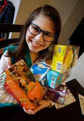 Girl Scout Lilia Dietz holds an armload of cookies in her Holmdel home Monday, January 21, 2019.