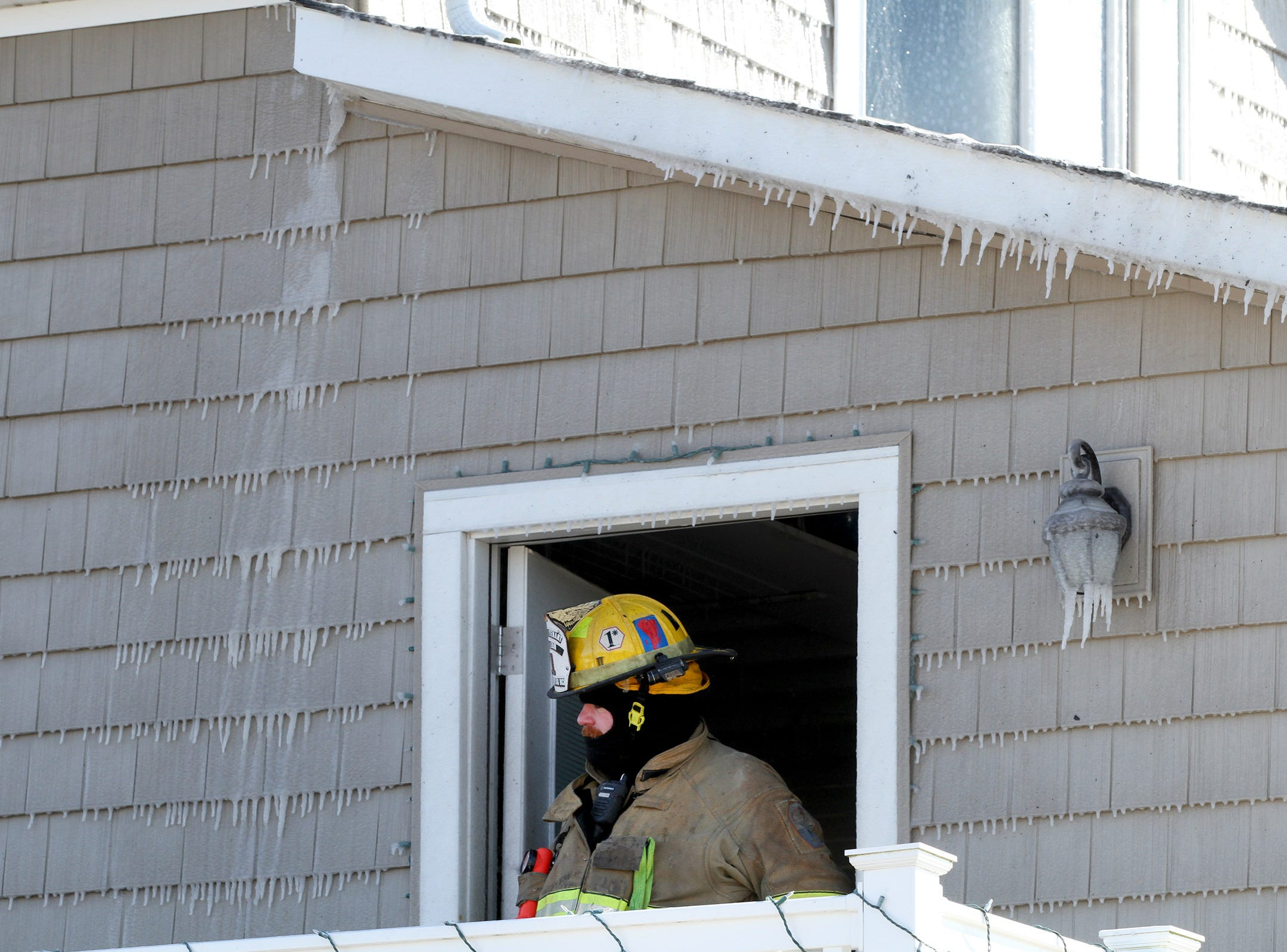 A firefighter exits a residence next to Point Lobster Company in Point Pleasant Beac Monday afternoon, January 21, 2019, after a fire was extinguished there.