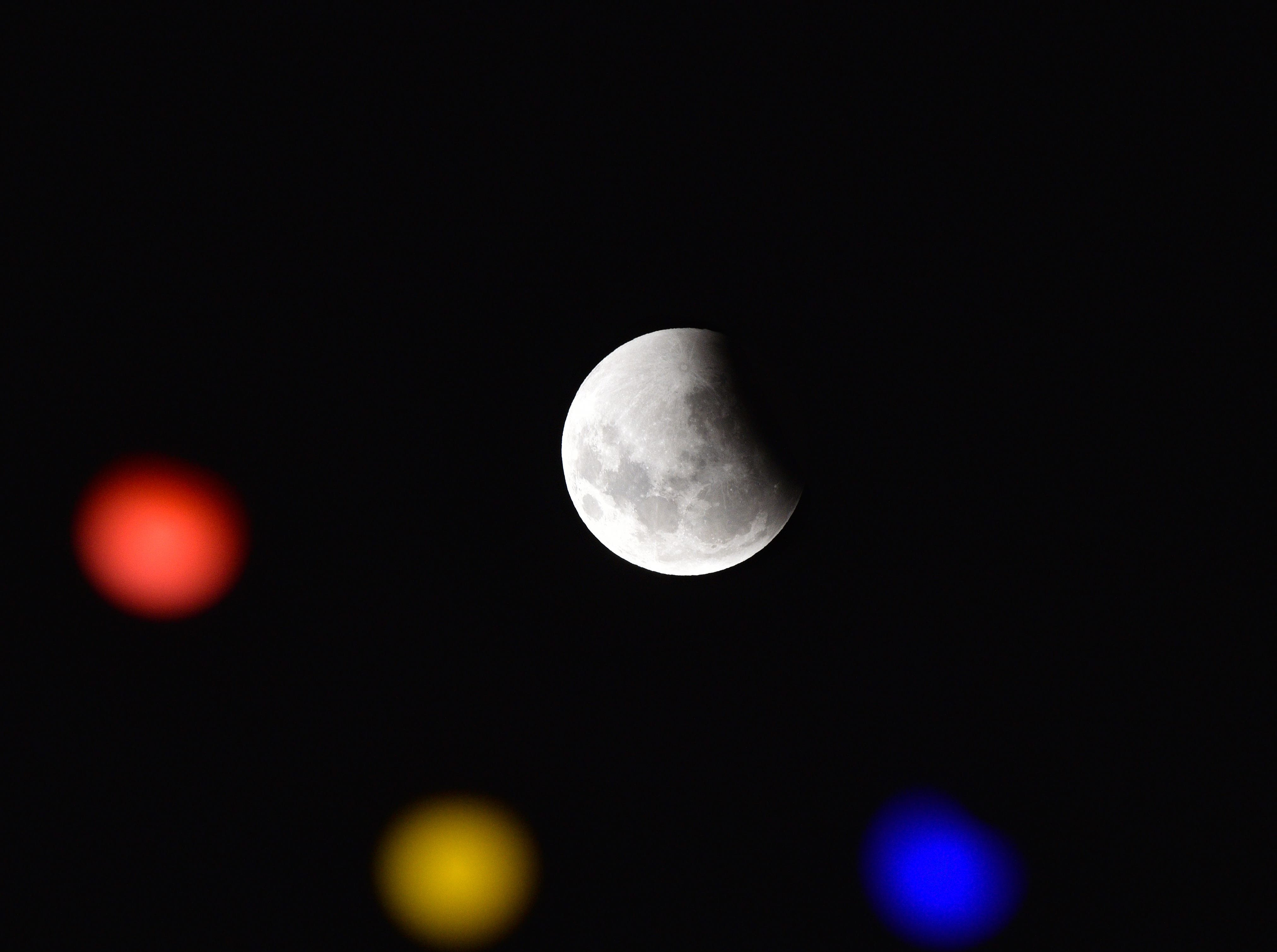 A total eclipse begins as the full moon shines over Montevideo on January 21, 2019 while colour lights decorate 18 de julio Avenue ahead of carnival festivities in Uruguay. - An unusual set of celestial circumstances comes together Sunday for skywatchers in Europe, Africa and the Americas, where a total lunar eclipse may be glimpsed, offering a view of a large, red Moon. (Photo by Mariana SUAREZ / AFP)MARIANA SUAREZ/AFP/Getty Images