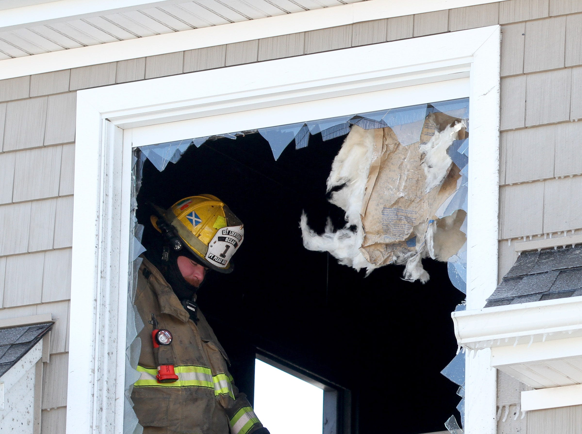 A firefighter is shown in a residence next to Point Lobster Company in Point Pleasant Beac Monday afternoon, January 21, 2019, after a fire was extinguished there.