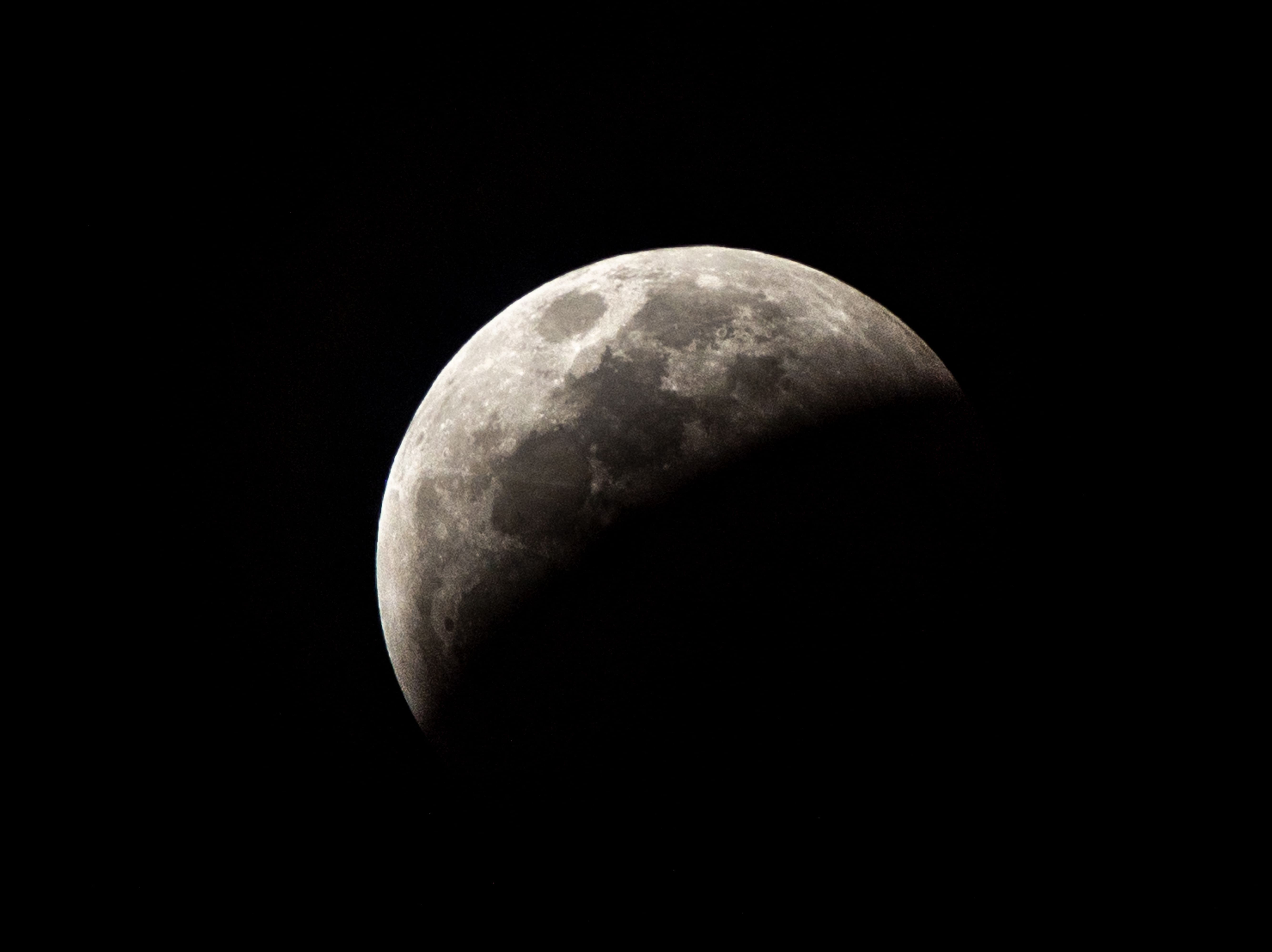 The so-called Super Blood Wolf Moon total lunar eclipse reaches a partial phase where more than half of the Moon is immersed in Earth's umbra, on Sunday January 20, 2019, in Miami, Florida. - The January 21 total lunar eclipse will be the last one until May 2021, and the last one visible from the United States until 2022. (Photo by Gaston De Cardenas / AFP)GASTON DE CARDENAS/AFP/Getty Images