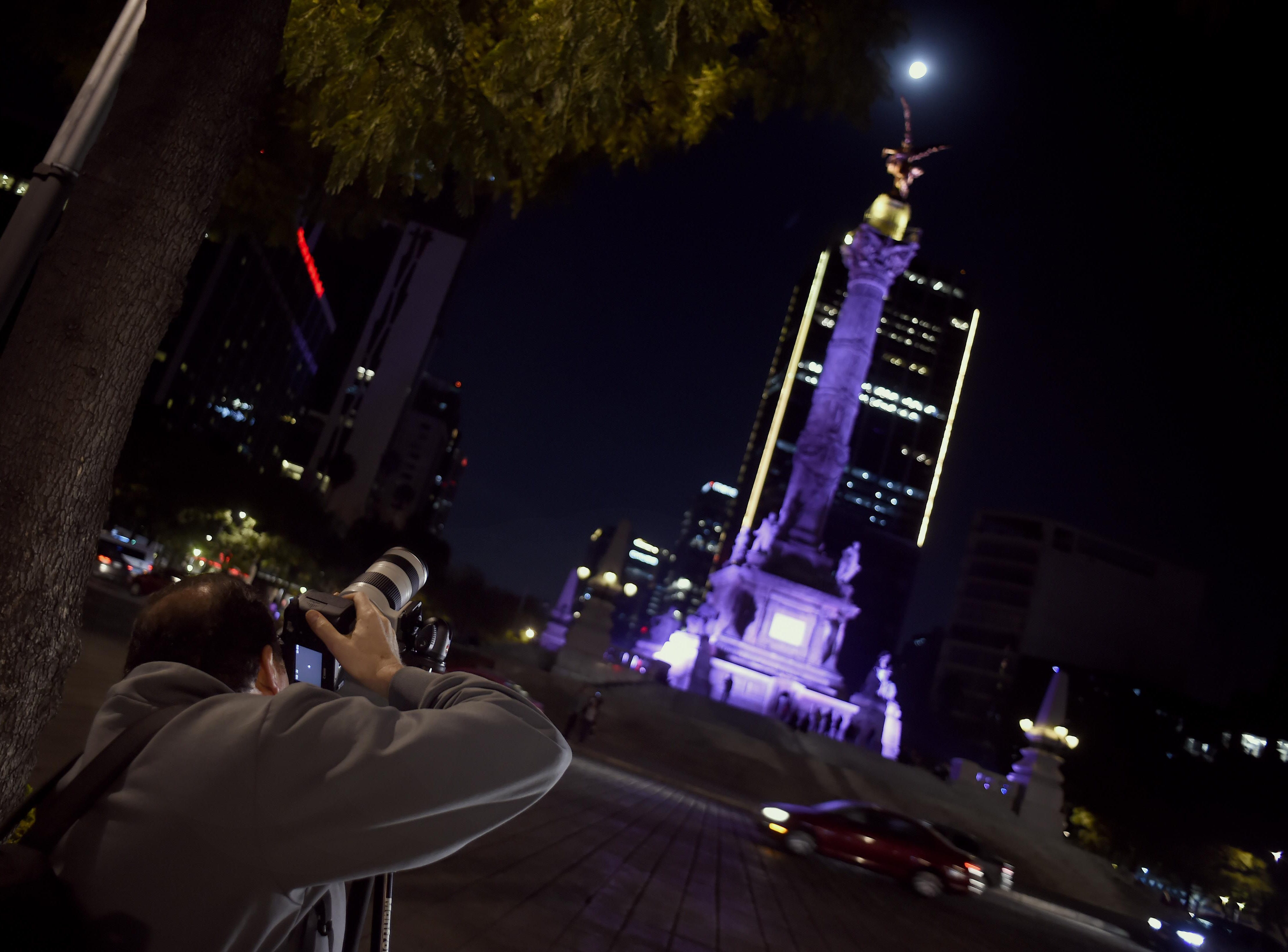 A man is taking pictures of the Super Moon during the start of the total lunar eclipse, at the Angel de la Independencia in Mexico City on January 20, 2019. (Photo by ALFREDO ESTRELLA / AFP)ALFREDO ESTRELLA/AFP/Getty Images