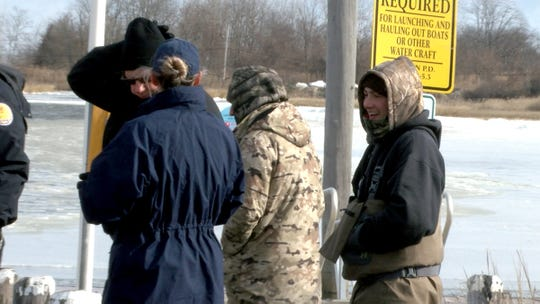 Two of the duck hunters who had made it back to shore earlier are shown with Coast Guardsmen who had rescue one of their fellow hunters who was stranded on a Navesink River island by ice Monday morning, January 21, 2019.