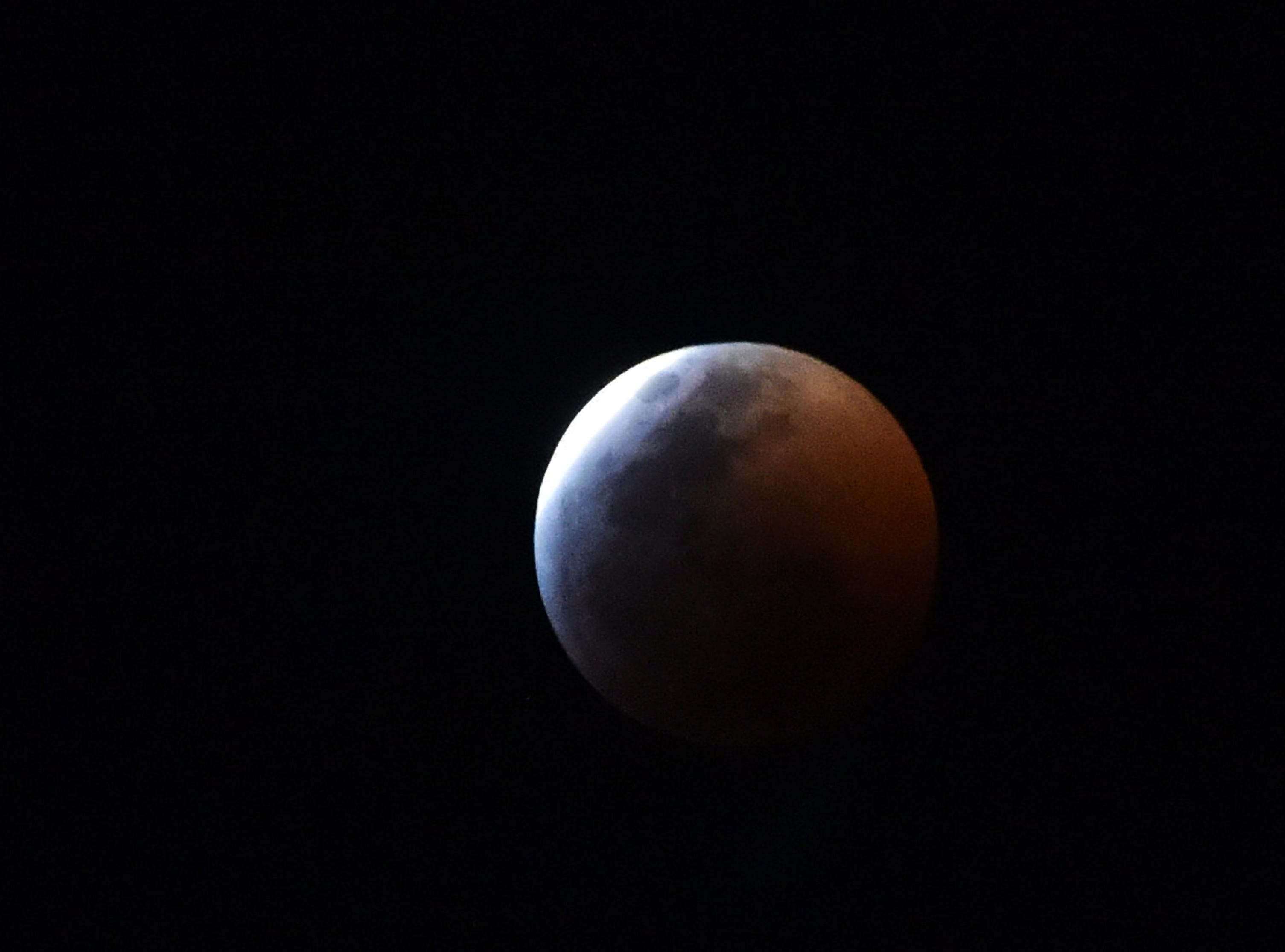 The so-called Super Blood Wolf Moon slips into Earth's dark umbral shadow during a total lunar eclipse over Mexico City on January 20, 2019. - An unusual set of celestial circumstances comes together Sunday for skywatchers in Europe, Africa and the Americas, where a total lunar eclipse may be glimpsed, offering a view of a large, red Moon. (Photo by RODRIGO ARANGUA / AFP)RODRIGO ARANGUA/AFP/Getty Images