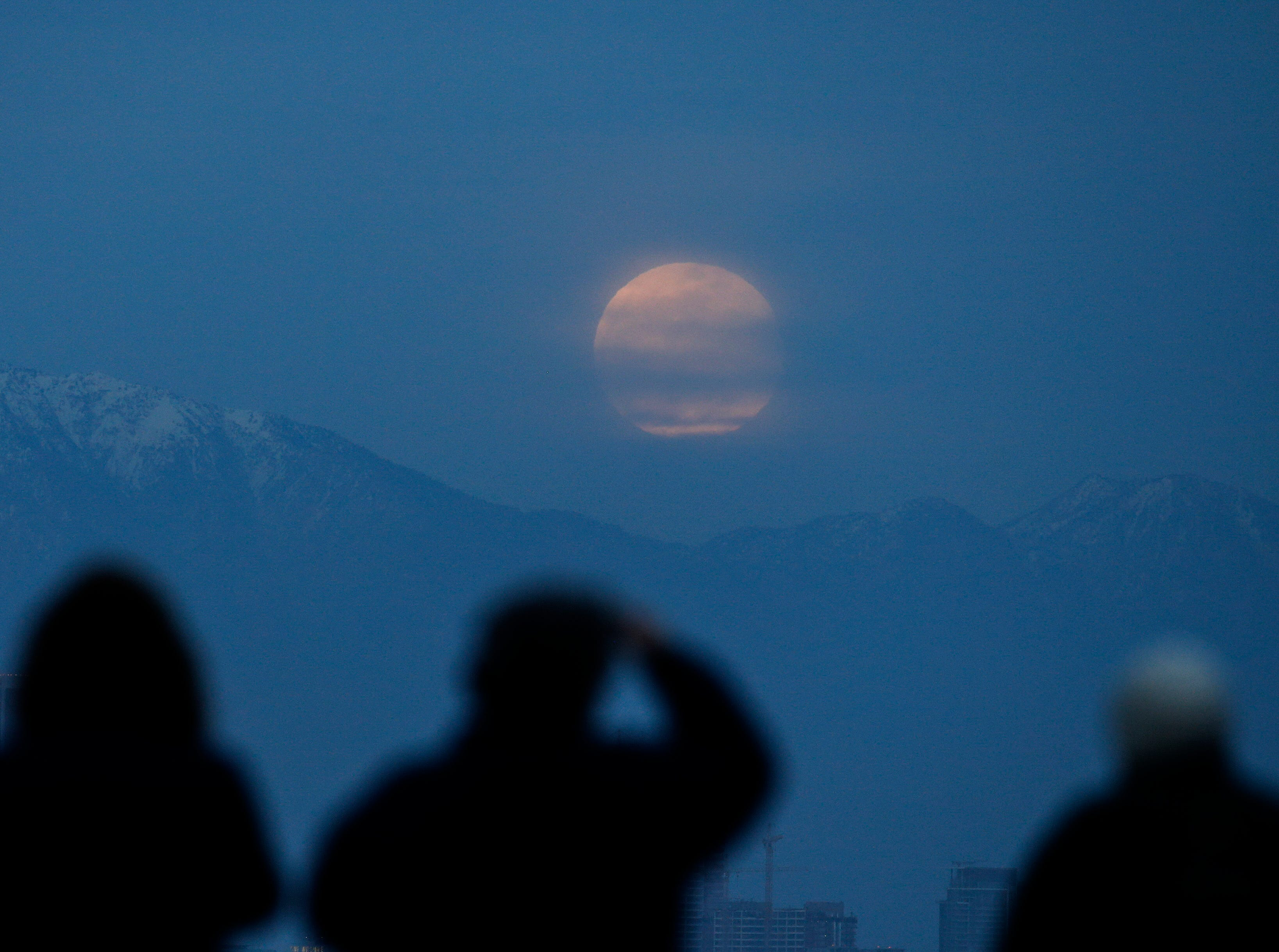 People watch the supermoon rise behind the downtown Los Angeles skyline, from Kenneth Hahn Park in Los Angeles, Sunday, Jan. 20, 2019. The year's first supermoon, when a full moon appears a little bigger and brighter thanks to its slightly closer position to Earth, is one of two lunar events Sunday. If skies are clear, a total eclipse will also be visible in North and South America, and parts of Europe. (AP Photo/Ringo H.W. Chiu)