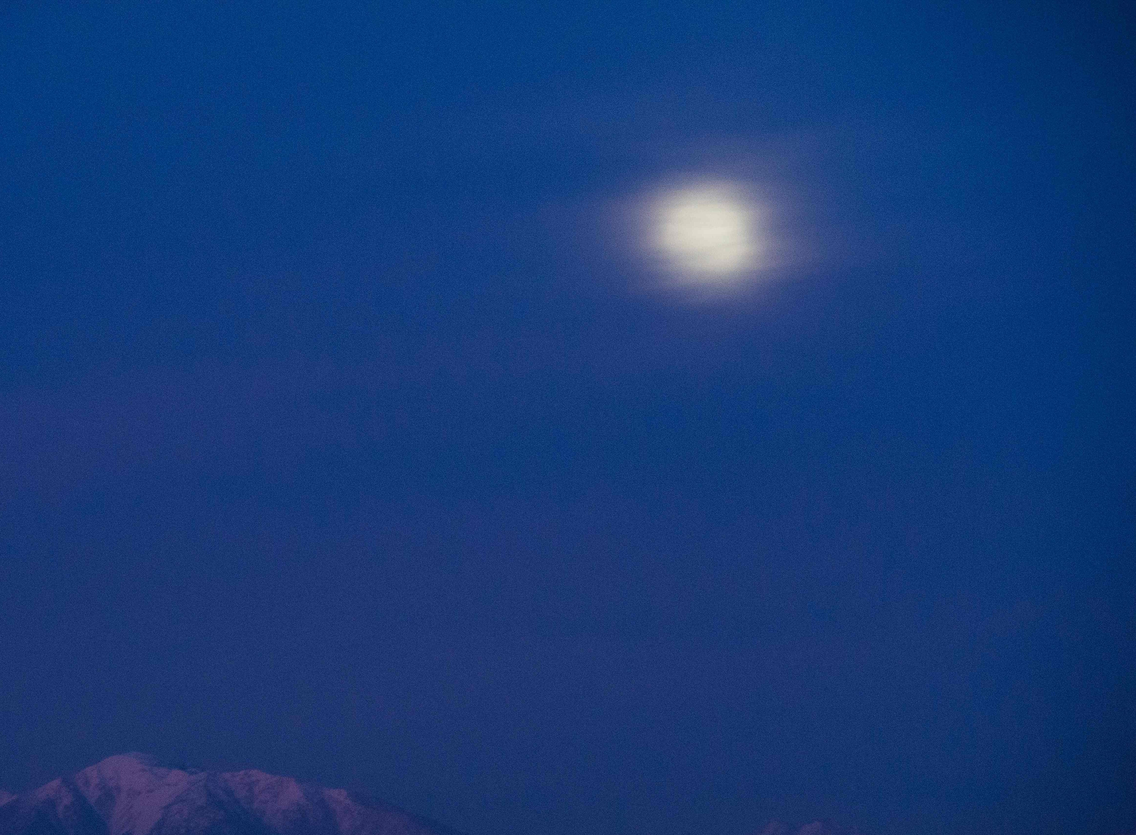 A Super Moon, partially obscured by clouds, rises over the Angeles National Forest as seen from Montecito Heights in Los Angeles, California, ahead of a total lunar eclipse, January 20, 2019. (Photo by Robyn Beck / AFP)ROBYN BECK/AFP/Getty Images