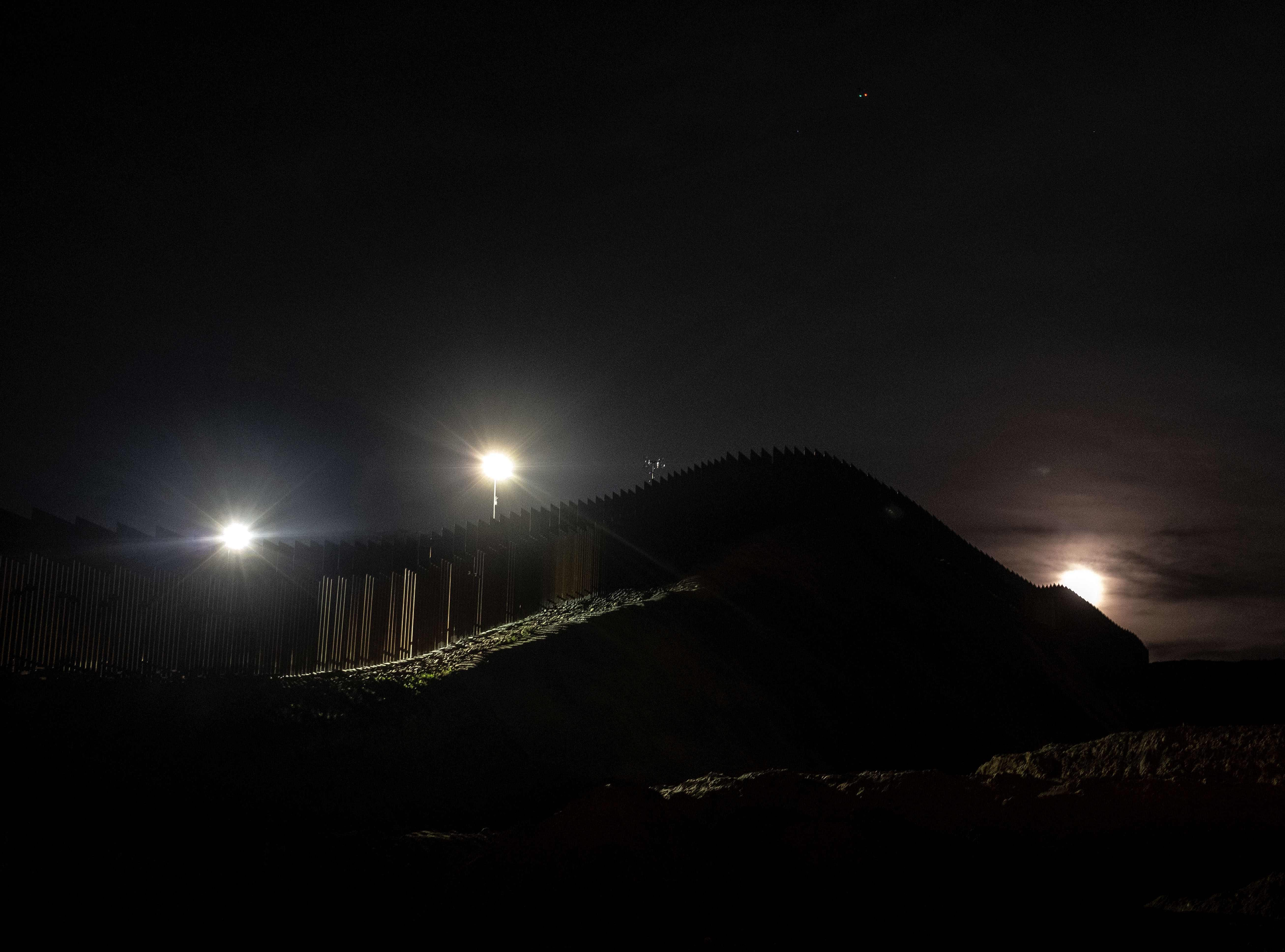 The US-Mexico border fence is silhouetted by the moon light in Tijuana, in Baja California state, Mexico, on January 20, 2019. (Photo by Guillermo Arias / AFP)GUILLERMO ARIAS/AFP/Getty Images