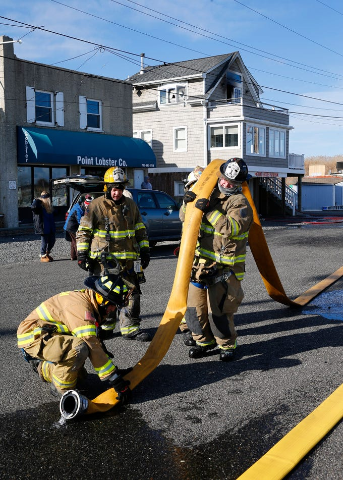 Point Pleasant Beach firefighters empty hoses after extinguishing a fire at a residence next to Point Lobster Company in the borough Monday afternoon, January 21, 2019.