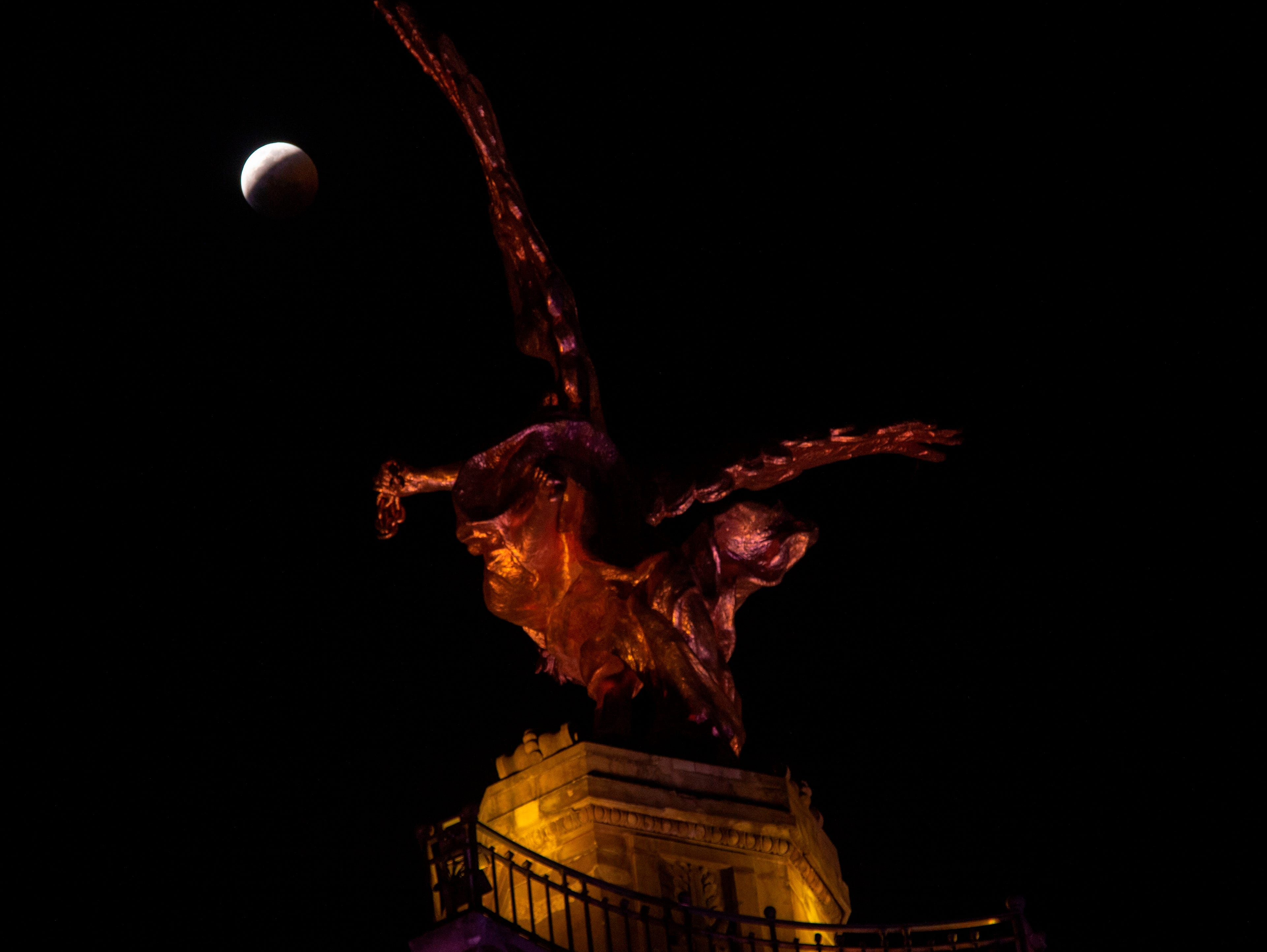 The so-called Super Blood Wolf Moon slips into Earth's dark umbral shadow during a total lunar eclipse over Angel de la Independencia in Mexico City on January 20, 2019. - An unusual set of celestial circumstances comes together Sunday for skywatchers in Europe, Africa and the Americas, where a total lunar eclipse may be glimpsed, offering a view of a large, red Moon. (Photo by ALFREDO ESTRELLA / AFP)ALFREDO ESTRELLA/AFP/Getty Images
