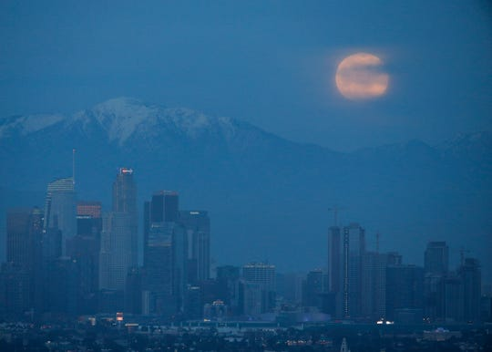 A supermoon rises behind the downtown Los Angeles skyline, as seen from Kenneth Hahn Park in Los Angeles, Sunday.