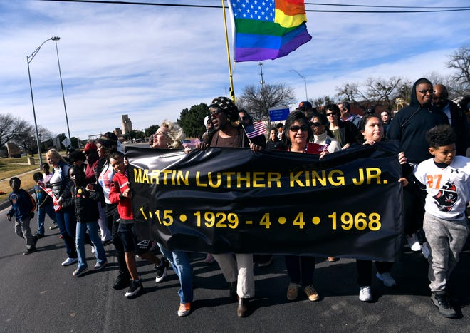 The Martin Luther King Jr. banner rounds the western edge of the bridge named after him Monday. At least 1,000 turned out for the annual MLK march in Abilene west, then east on East Highway 80.